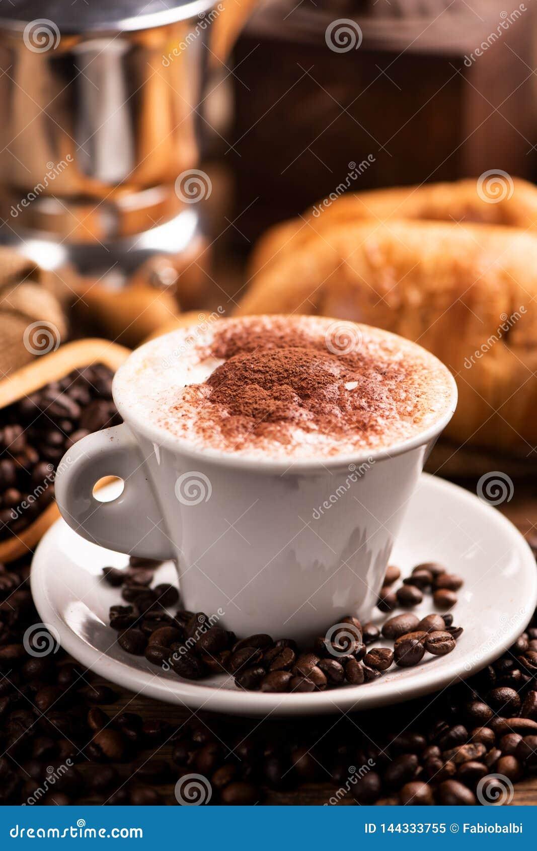 Taza de café rodeada por los granos de café