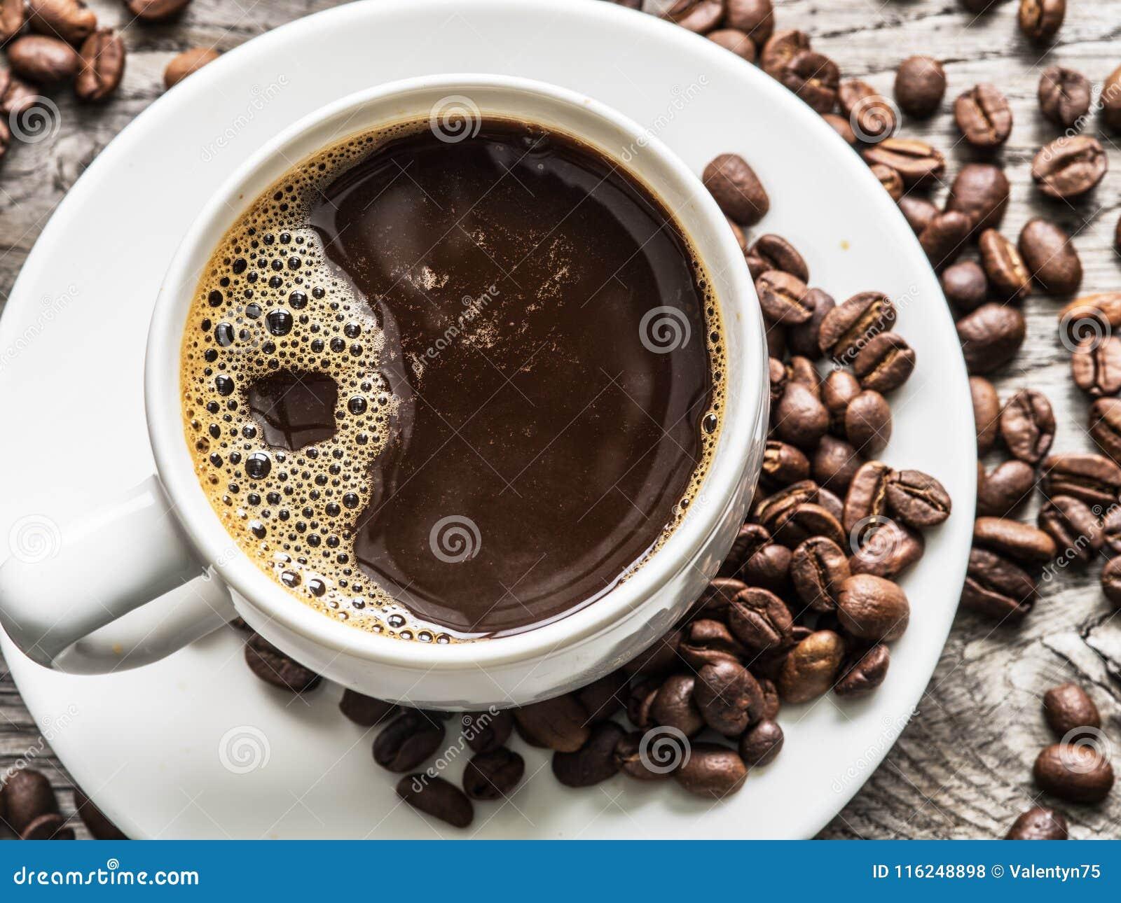 Taza de café rodeada por los granos de café Visión superior