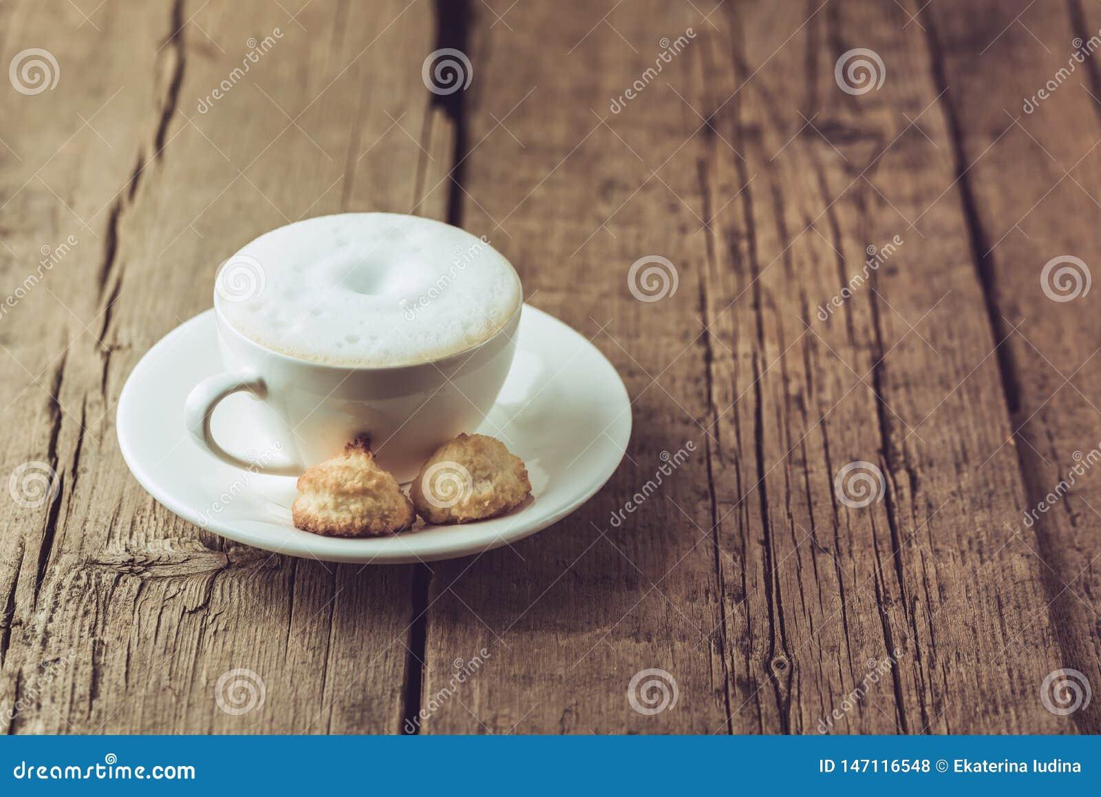 Taza de café y de galletas hechas en casa del coco en el postre sabroso del coco del viejo del fondo espacio horizontal de madera