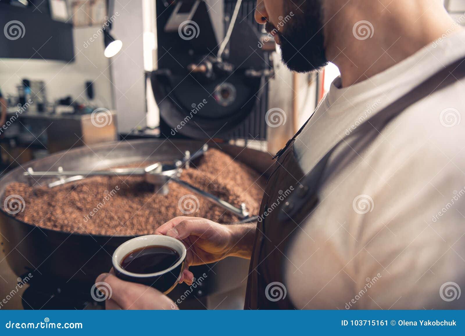 Taza barbuda seria de la prueba del hombre de café mientras que mira  preparado habas en máquina especial del asador Relaje el concepto Cierre  para arriba b8e333bb0fba