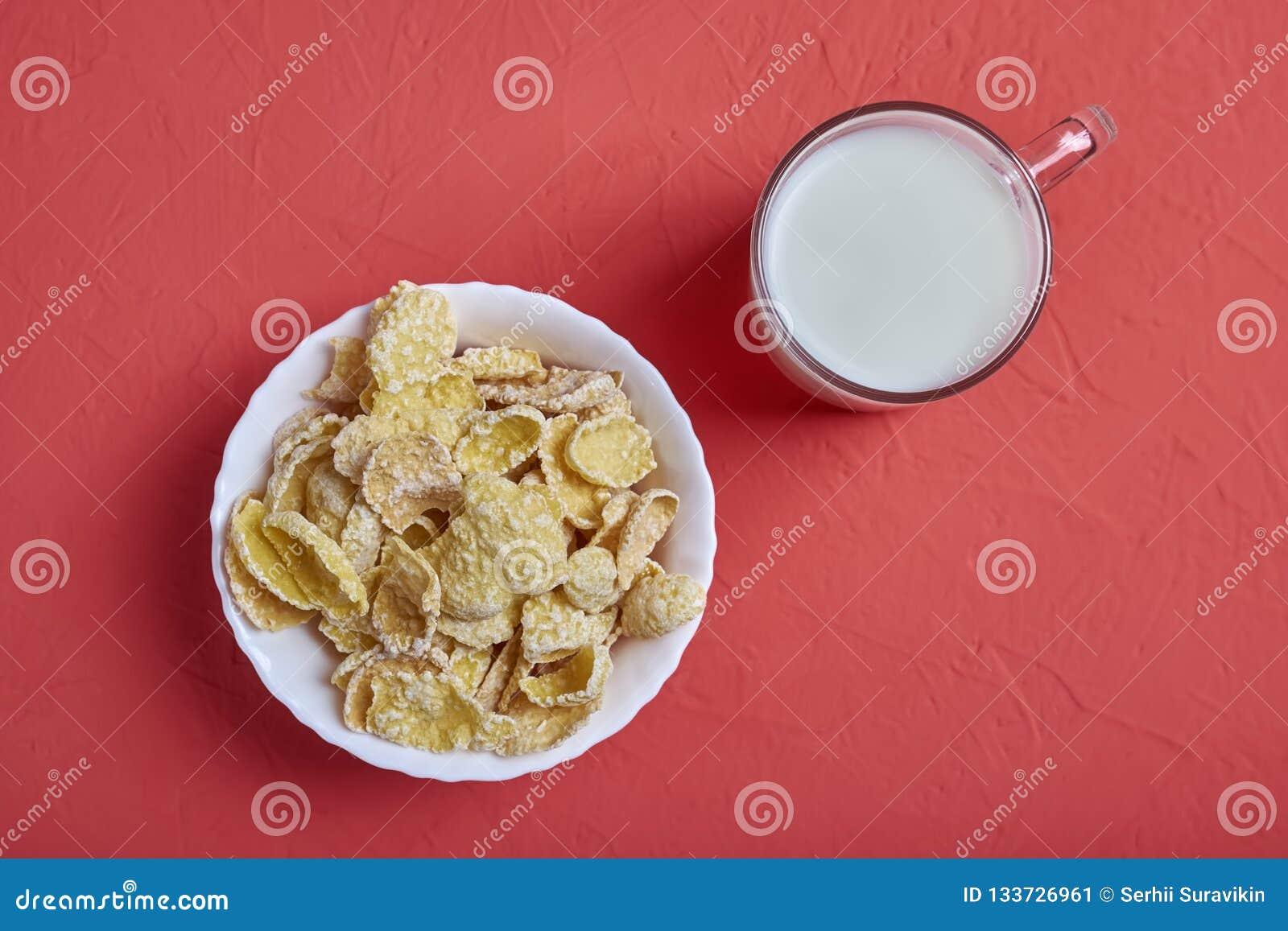 Taza de leche y de avenas en el cuenco blanco