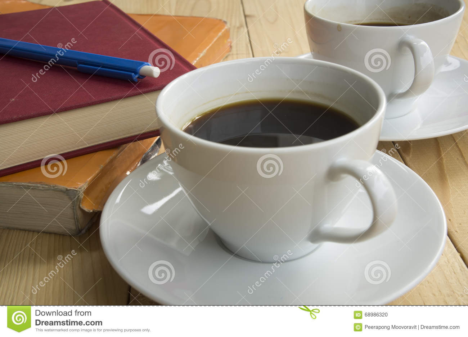 Taza de mañana del café con la pluma roja del azul del libro