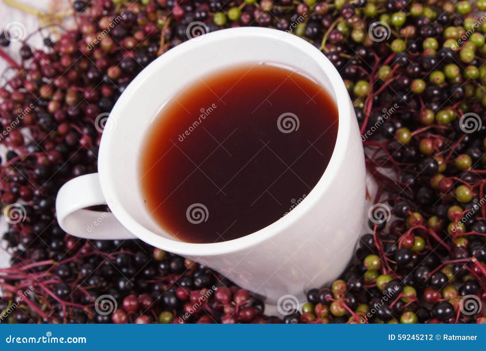 Taza de té caliente con el jugo de la baya del saúco y montón de la baya, nutrición sana