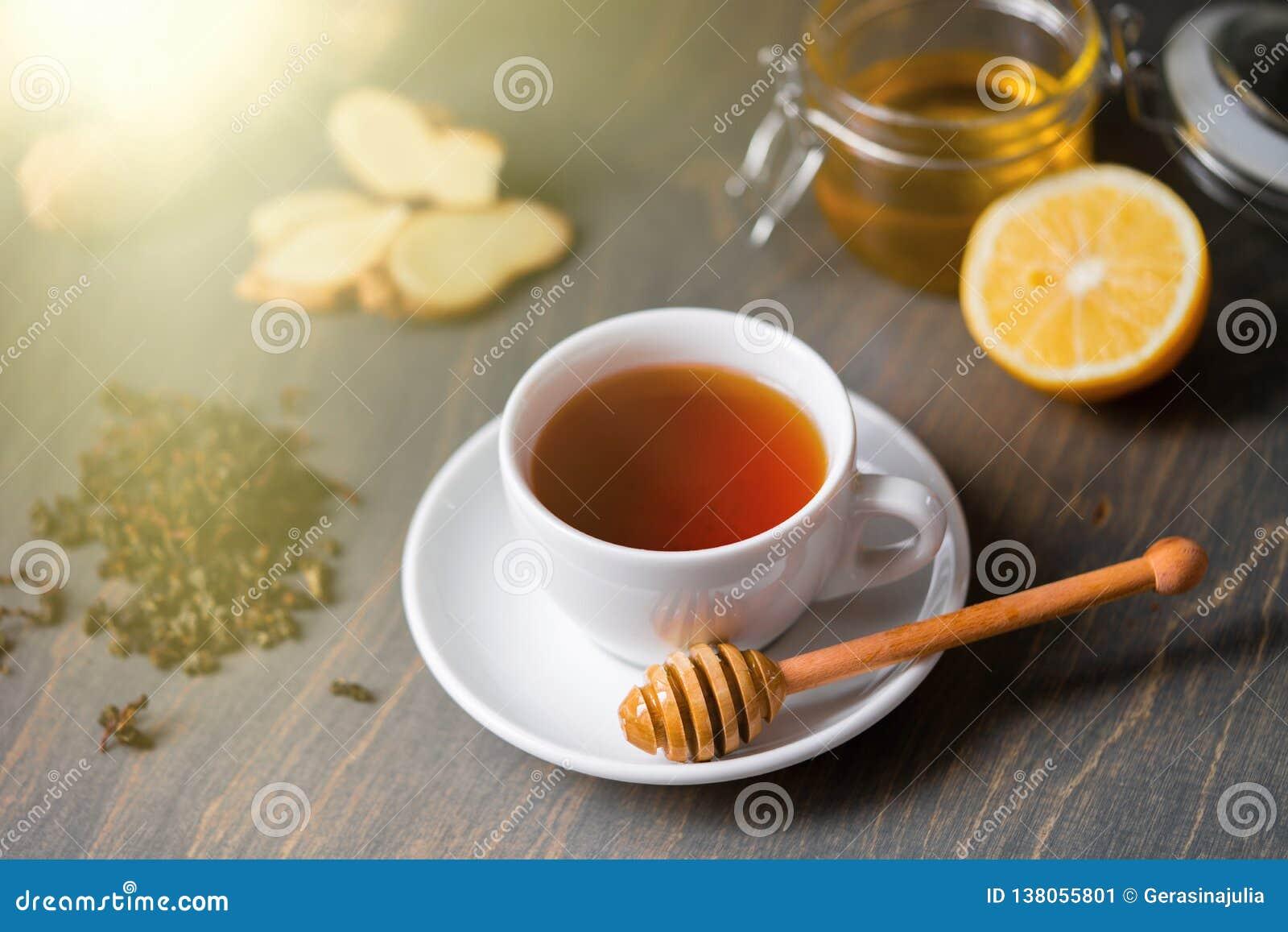 Taza de té con el limón, el jengibre, la miel y el palillo de la miel en la tabla rústica de madera