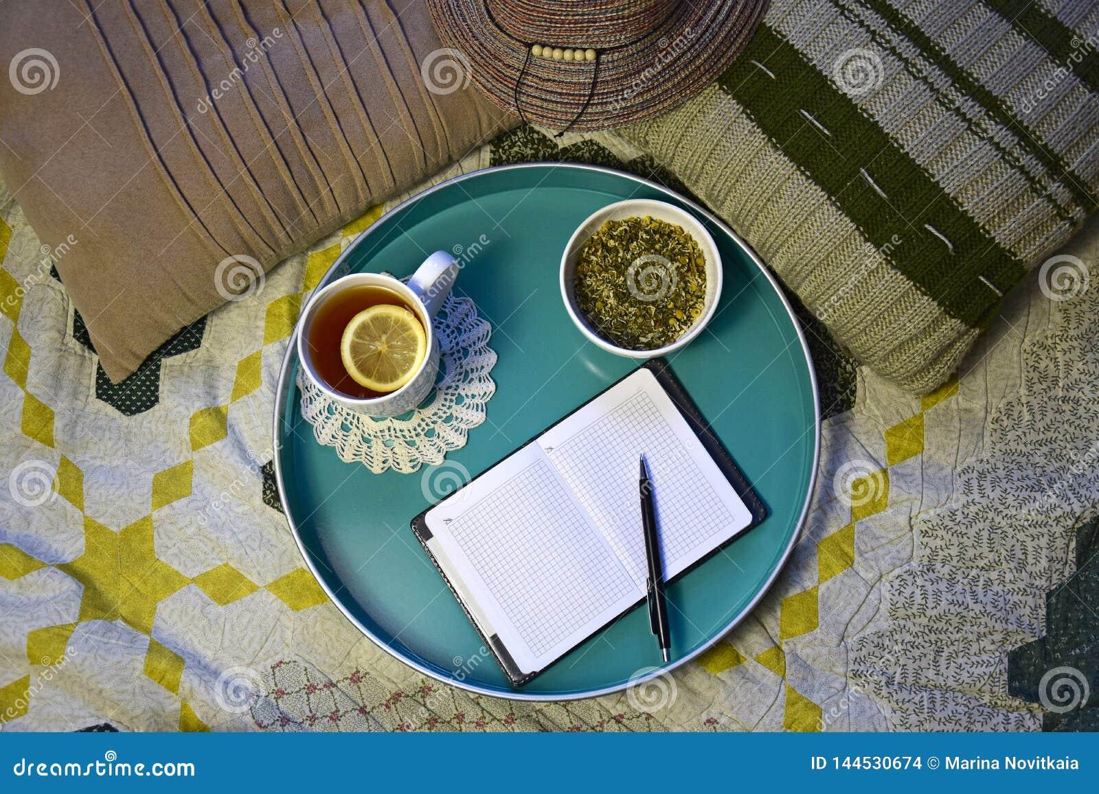 Taza de té con el limón, la infusión de hierbas natural y el cuaderno con la pluma