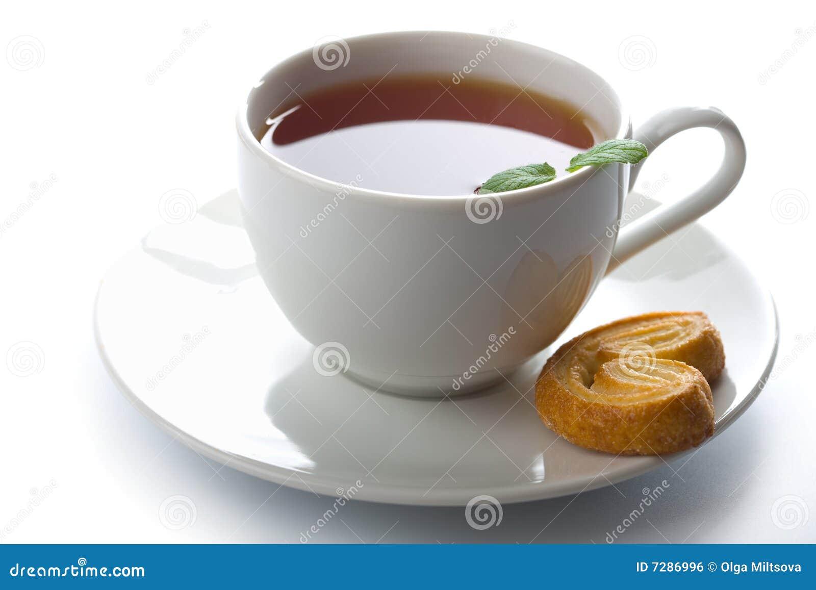 Taza de té con la menta y la galleta aisladas