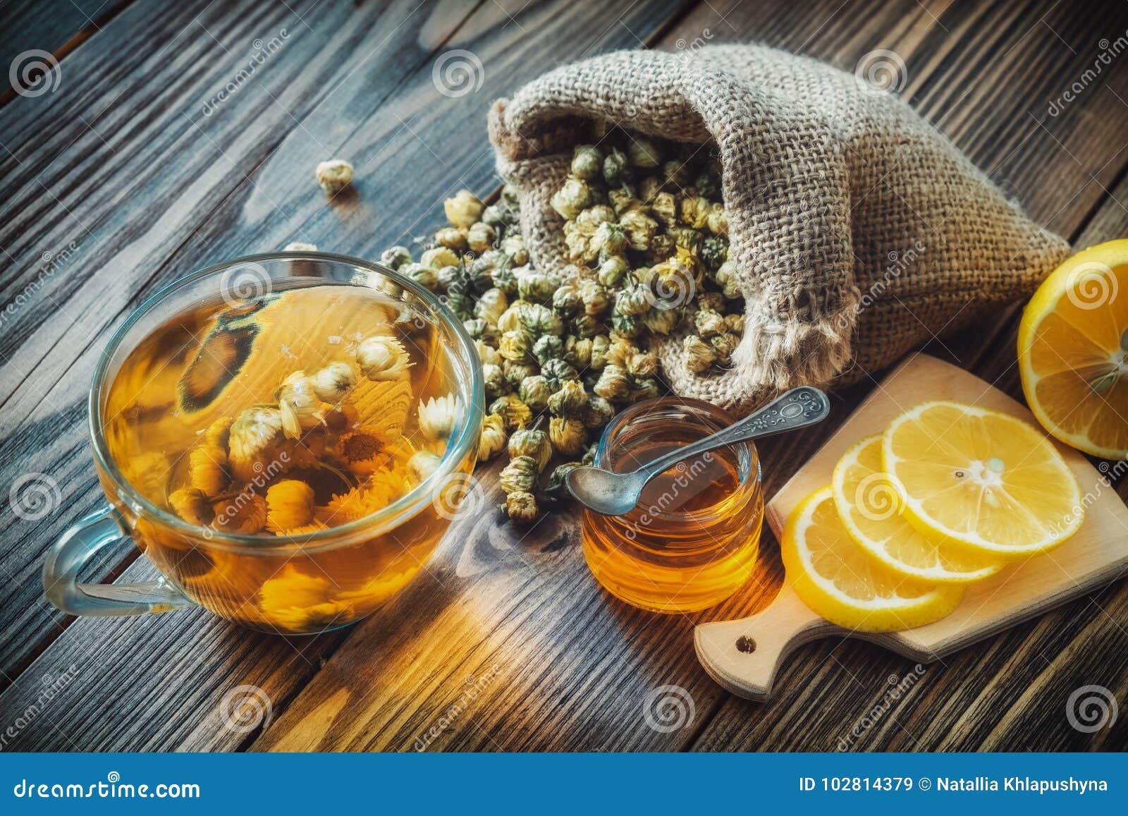 Taza de té sana de manzanilla, bolso de la arpillera de las flores secas de las margaritas, tarro de la miel y rebanadas del limó