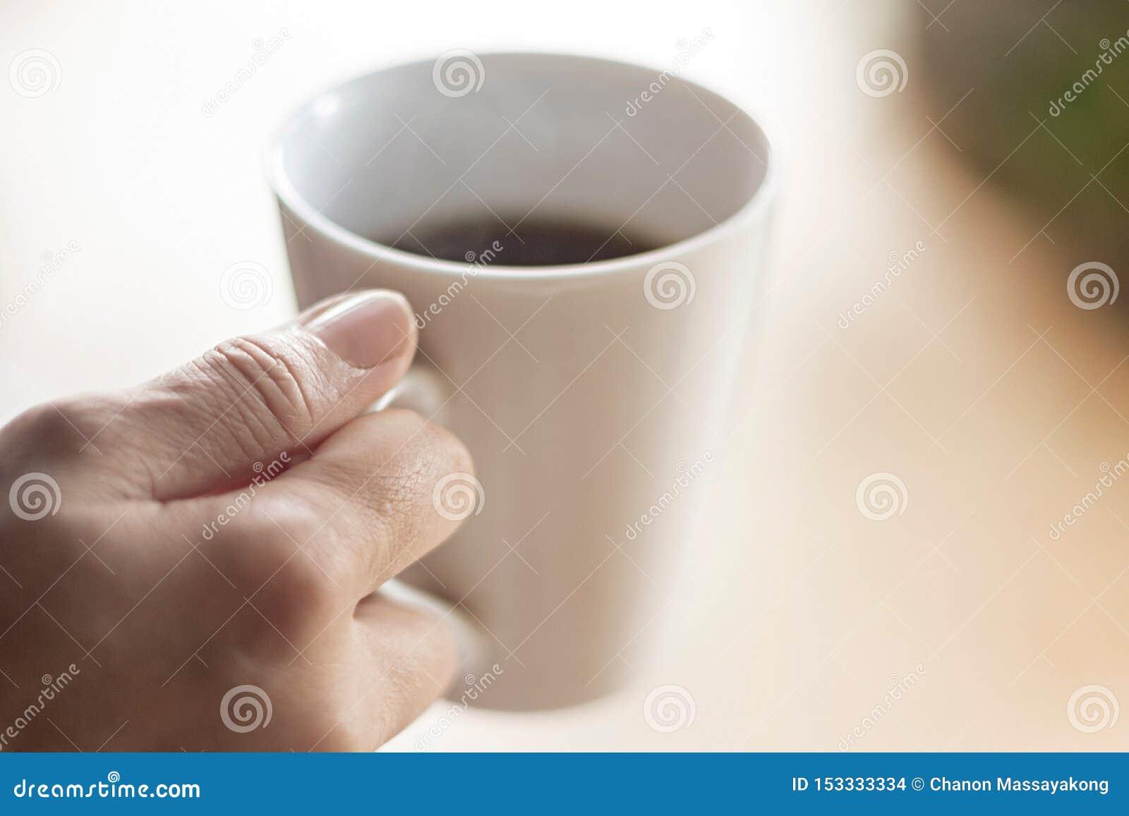 Taza femenina del control de la mano de café