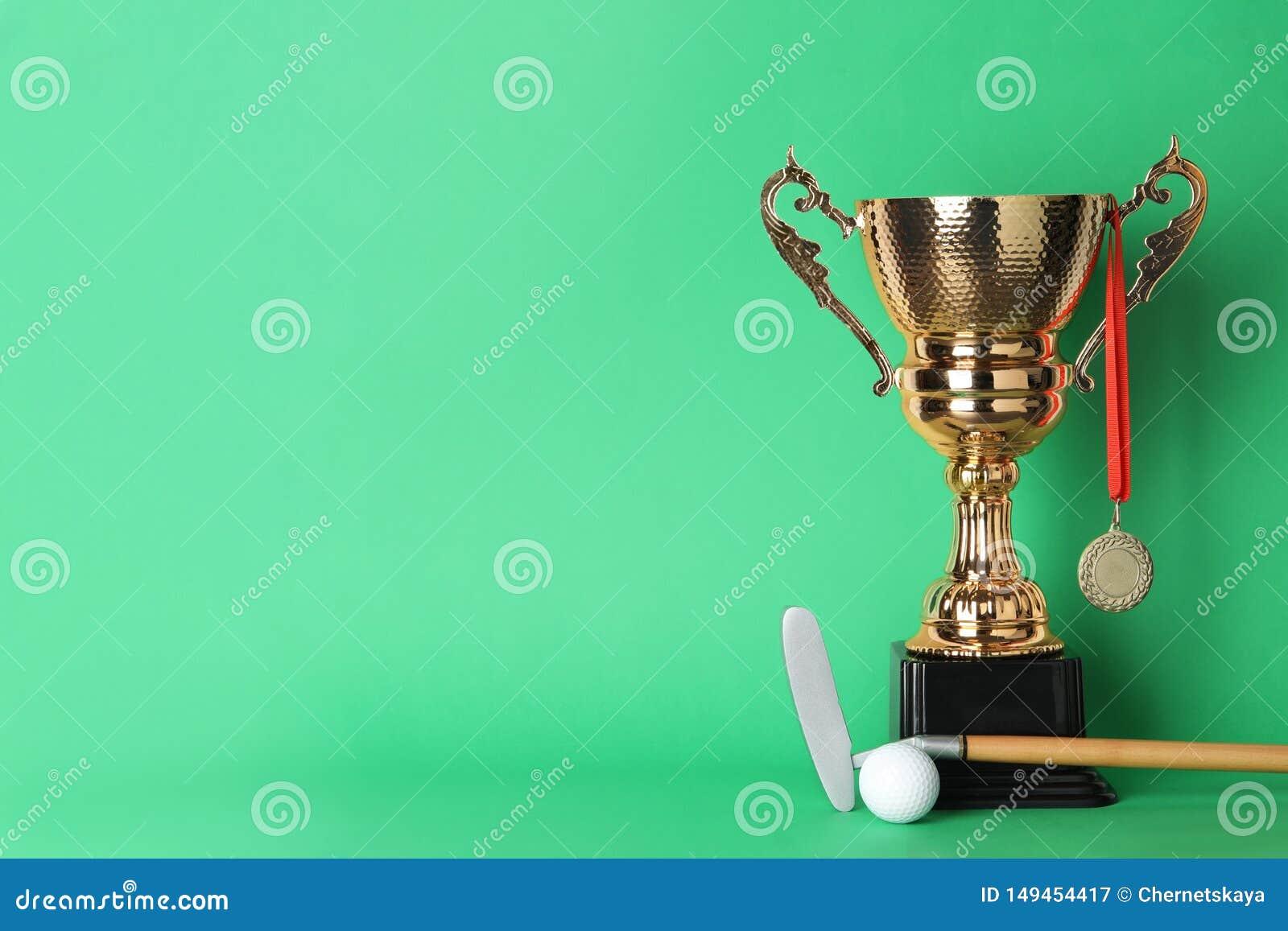 Taza, medalla, club de golf y bola de oro del trofeo en fondo del color
