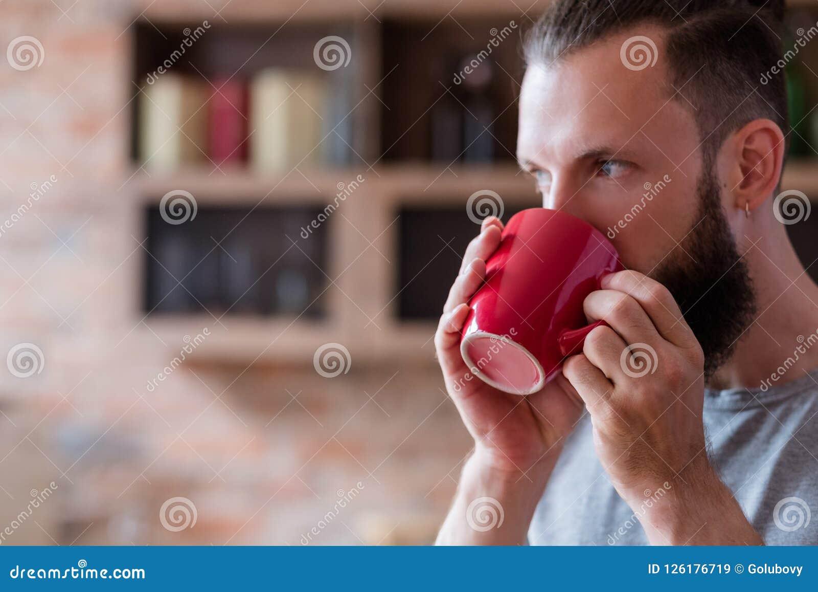 Taza relajante del rojo del hombre de la bebida del hábito del descanso para tomar café del té