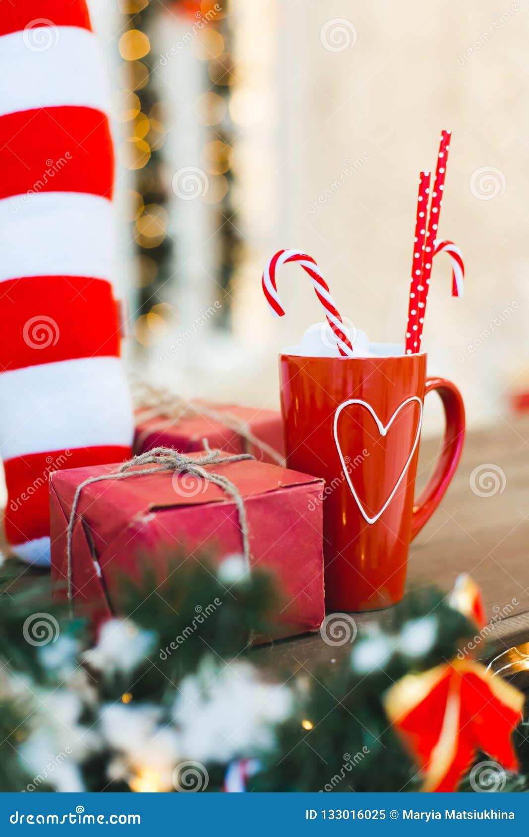Taza roja de té o de café o chokolate caliente con los dulces y el regalo - fondo del día de fiesta de la Navidad