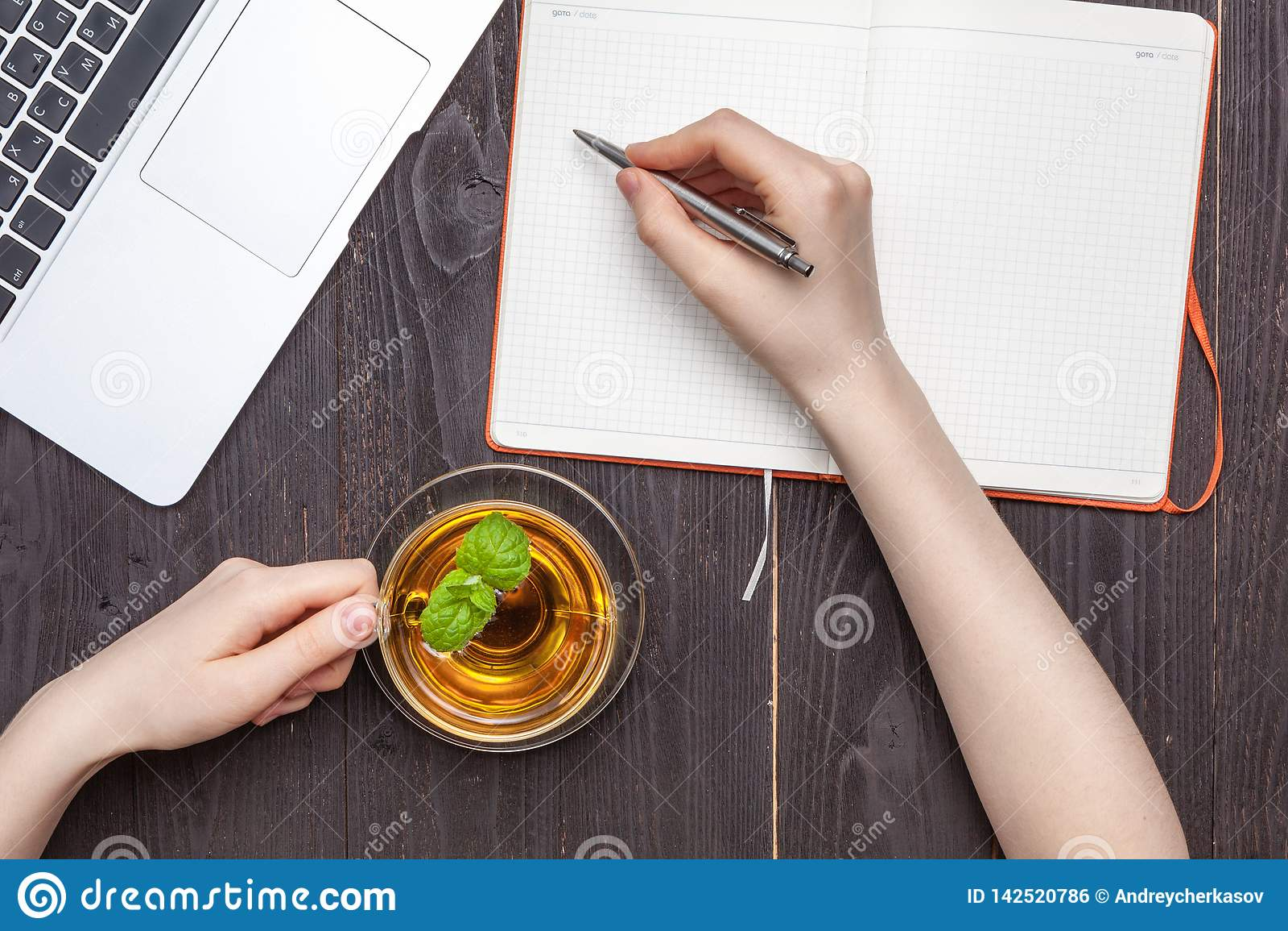 Taza transparente de té negro ambrino en manos femeninas