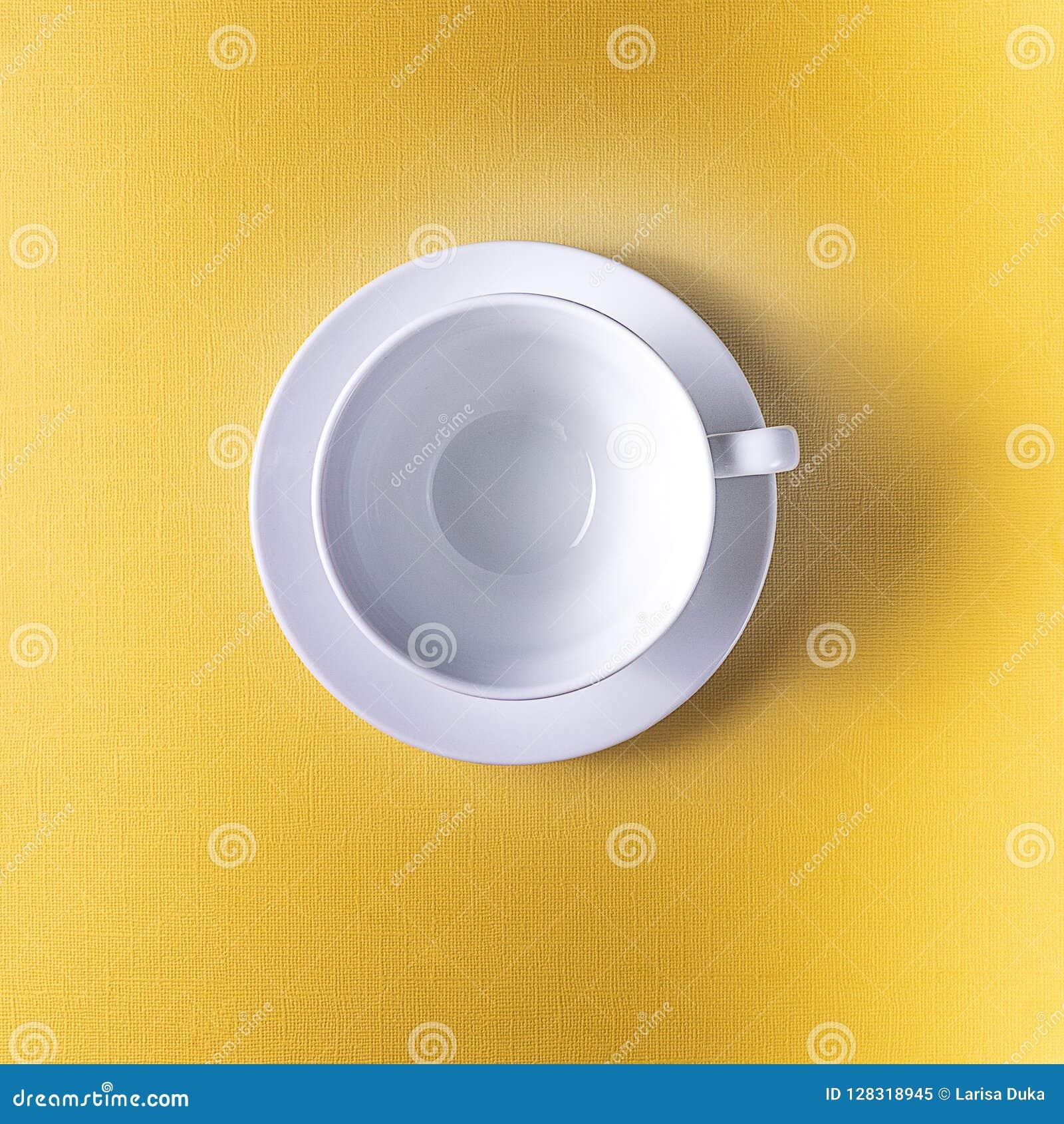 Taza vacía del café o de té en el fondo amarillo del color, espacio de la copia