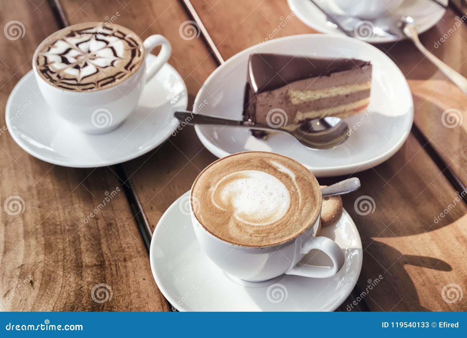 Tazas de café del capuchino y de torta del mousse de chocolate Imagen entonada