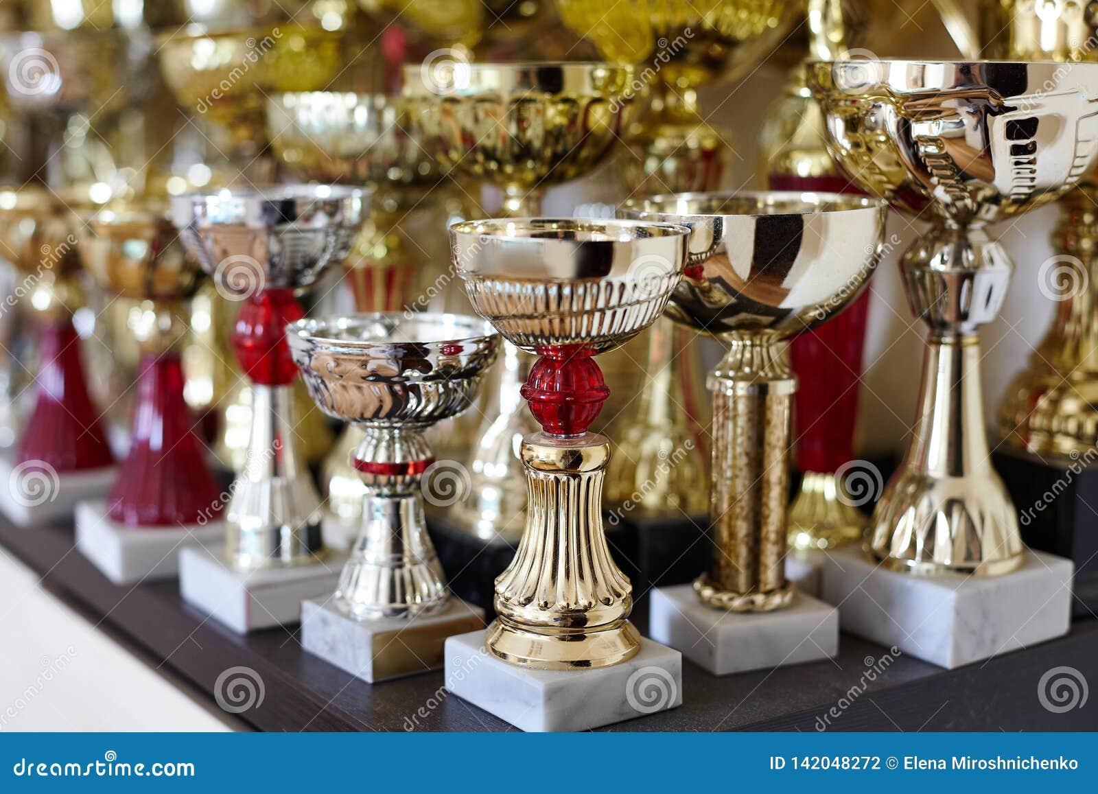 Tazas de los deportes, trofeos en el estante, de oro y de plata Concepto de la victoria