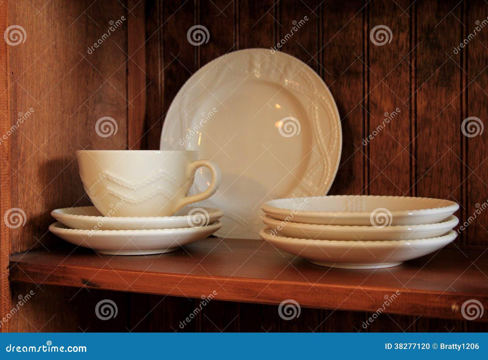 Tazas y platillos en los estantes de madera