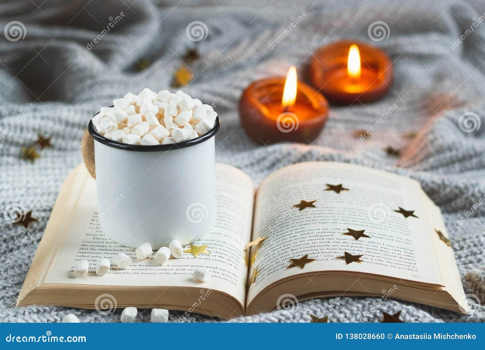 Tazza bianca con cacao e la caramella gommosa e molle su un libro aperto su un BAC strutturato grigio chiaro
