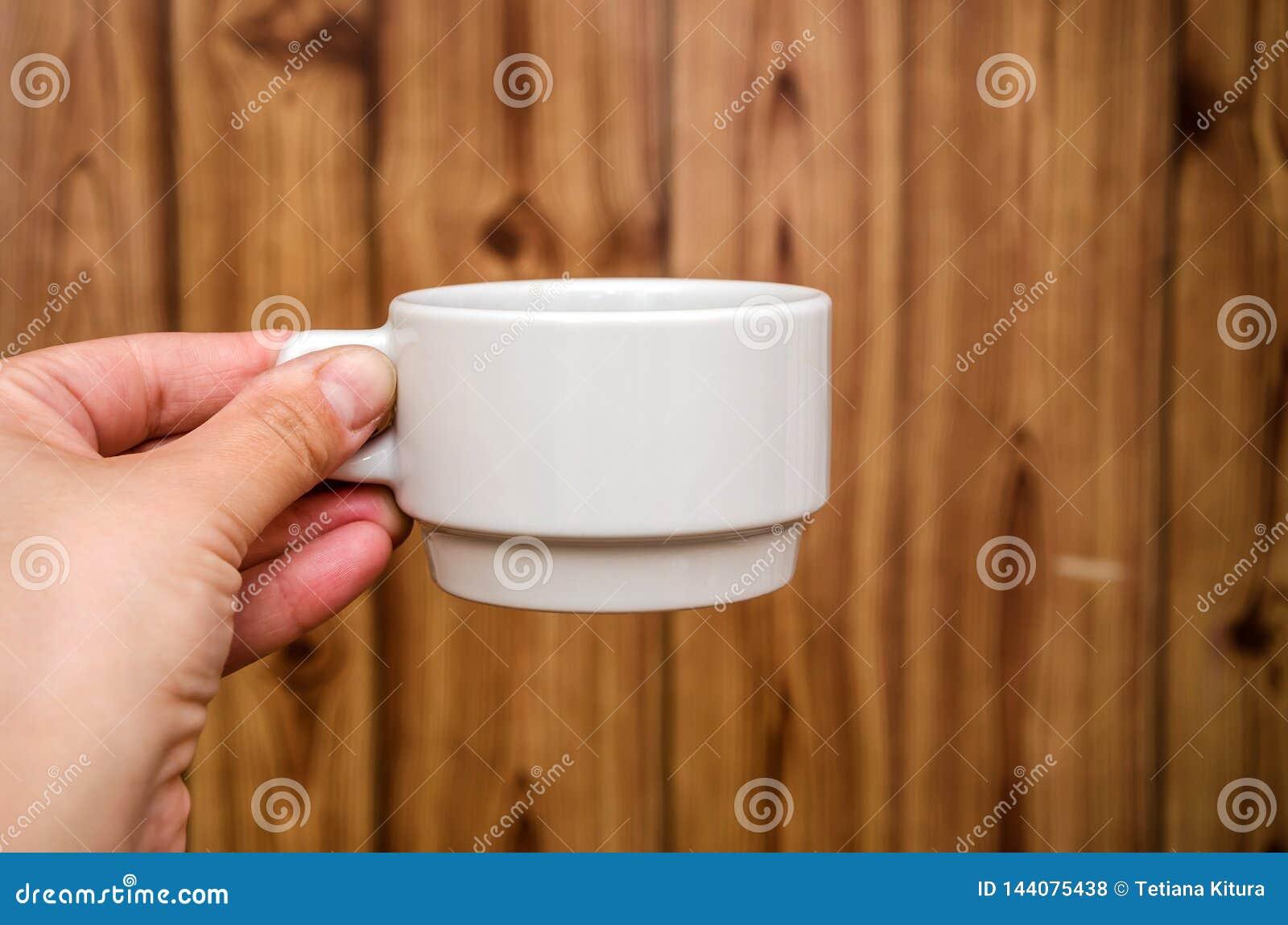 Tazza bianca a disposizione su fondo di legno