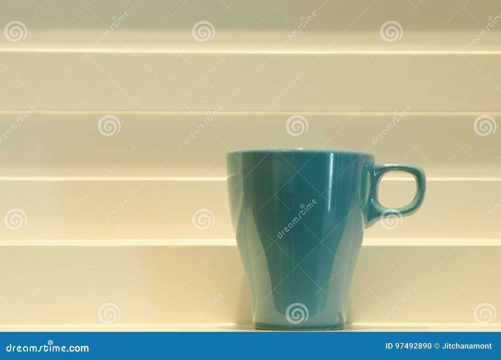 Tazza blu sul fondo di bianco di punto