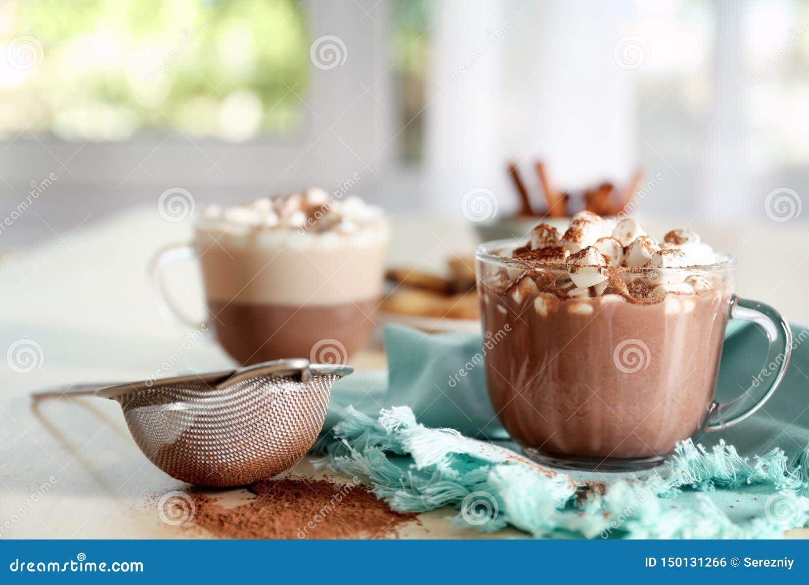 Tazza con la bevanda calda con le caramelle gommosa e molle e la polvere di cacao sulla tavola
