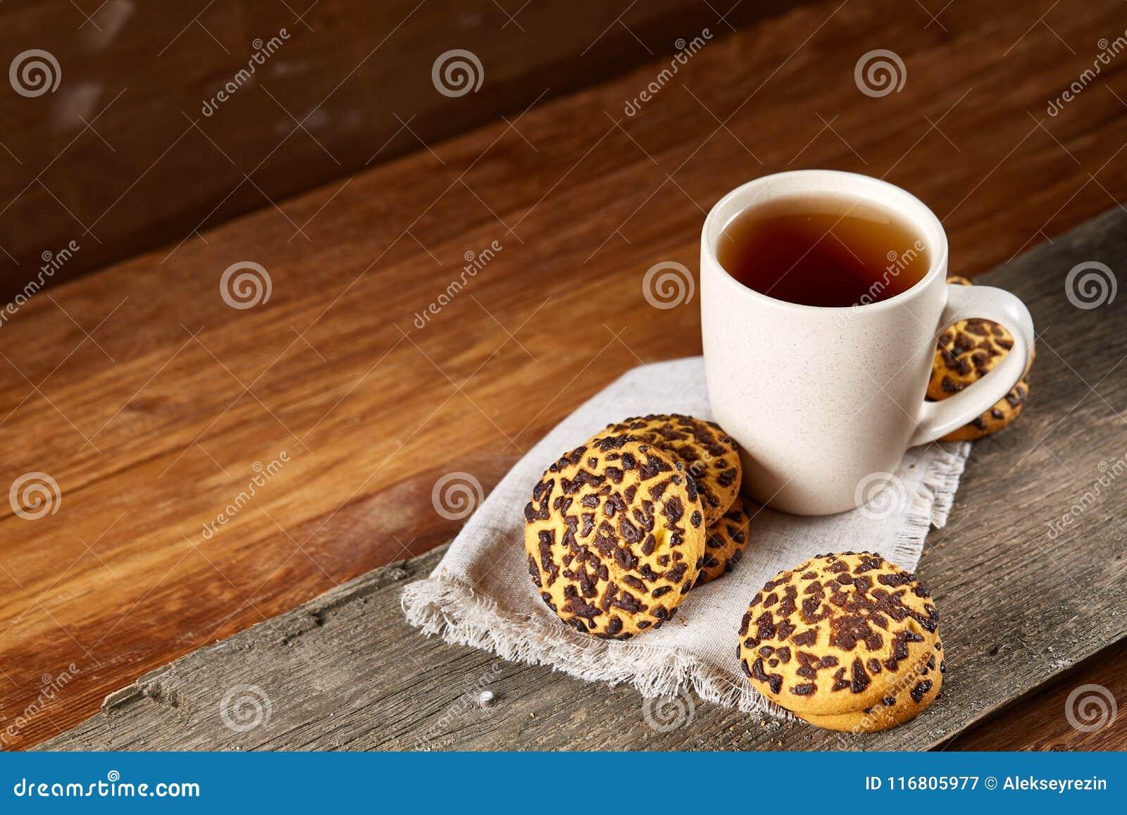 Tazza dei biscotti di pepita di cioccolato e del tè sul tovagliolo homespun bianco nel fuoco stile country e selettivo