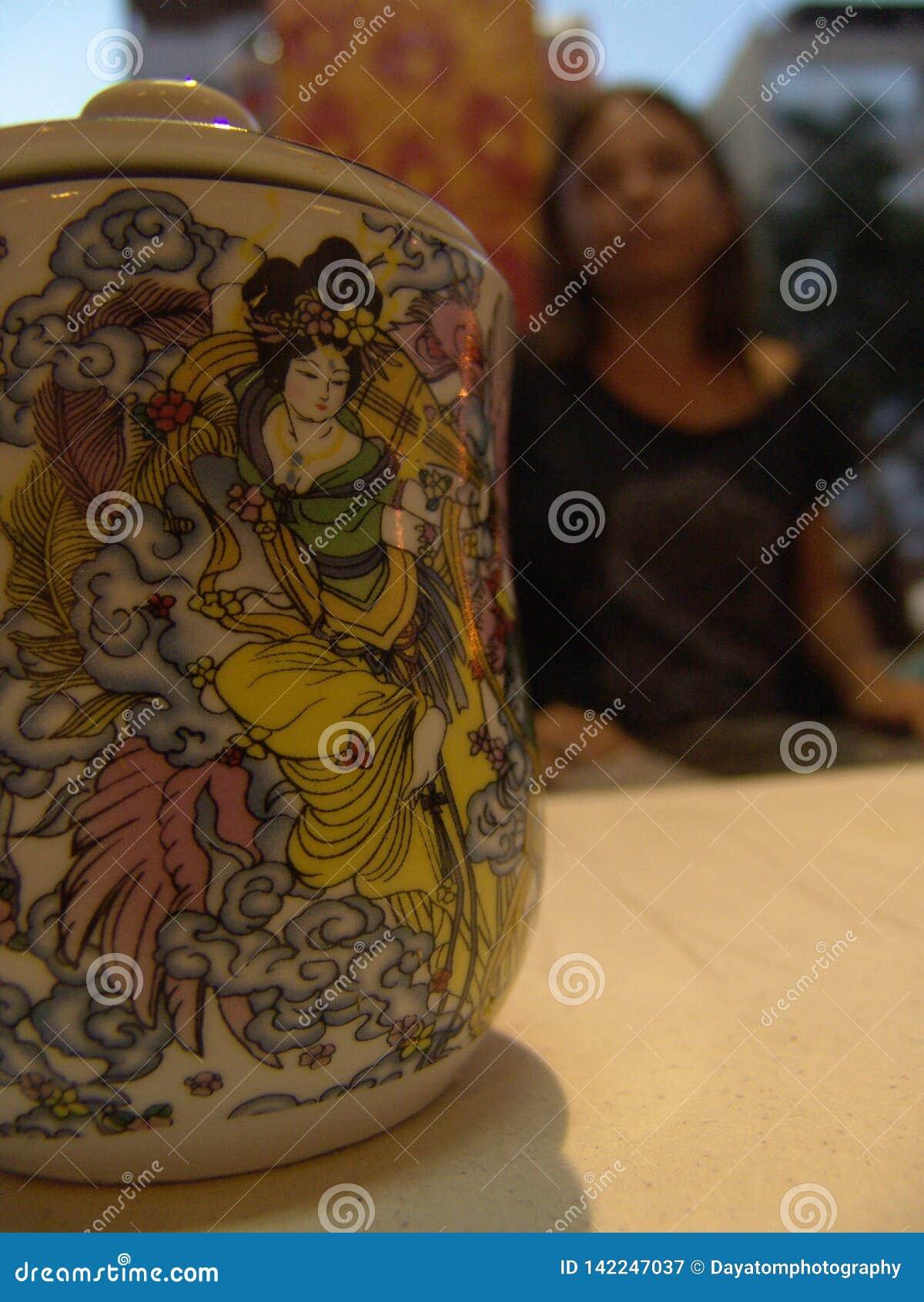 Tazza del tè con un coperchio, con bella pittura asiatica e su una maniglia del dito, stante sulla tavola bianca