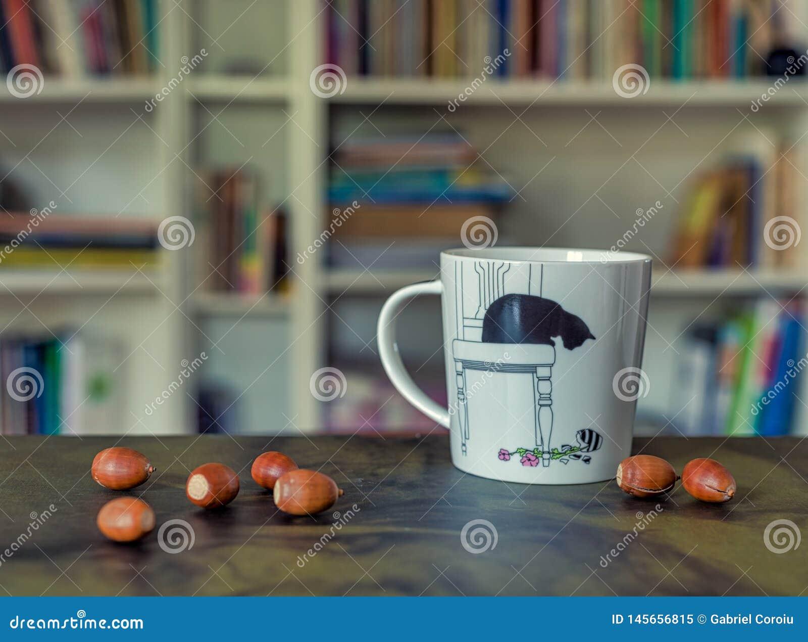 Tazza del t? di divertimento con le ghiande sulla tavola