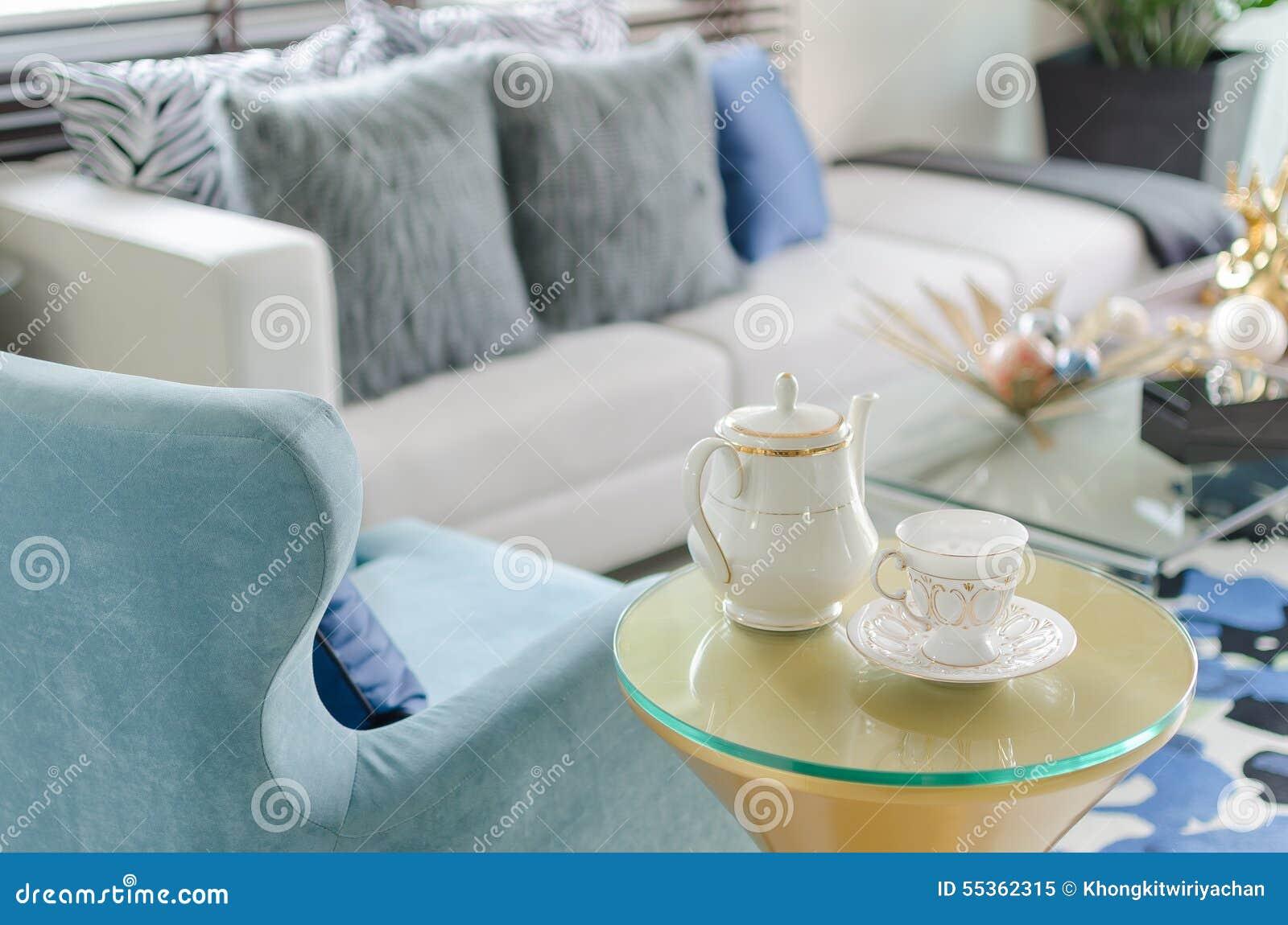 Tazza dell insieme di tè con la sedia blu di stile classico in salone