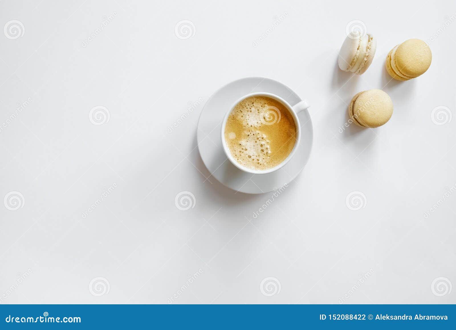 Tazza di caffè bianca con i macarons gialli