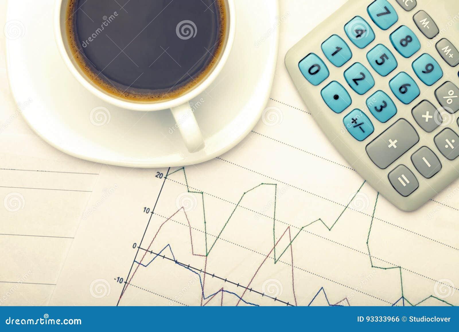 Tazza di caffè e calcolatore sopra i grafici del mercato azionario - vista dalla cima Immagine filtrata: effetto d annata elabora