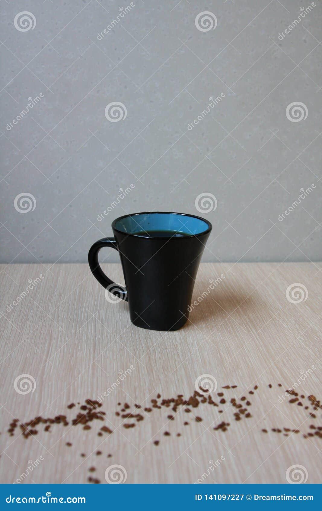 Tazza di caffè fresco su fondo leggero con il caffè della polvere del grano