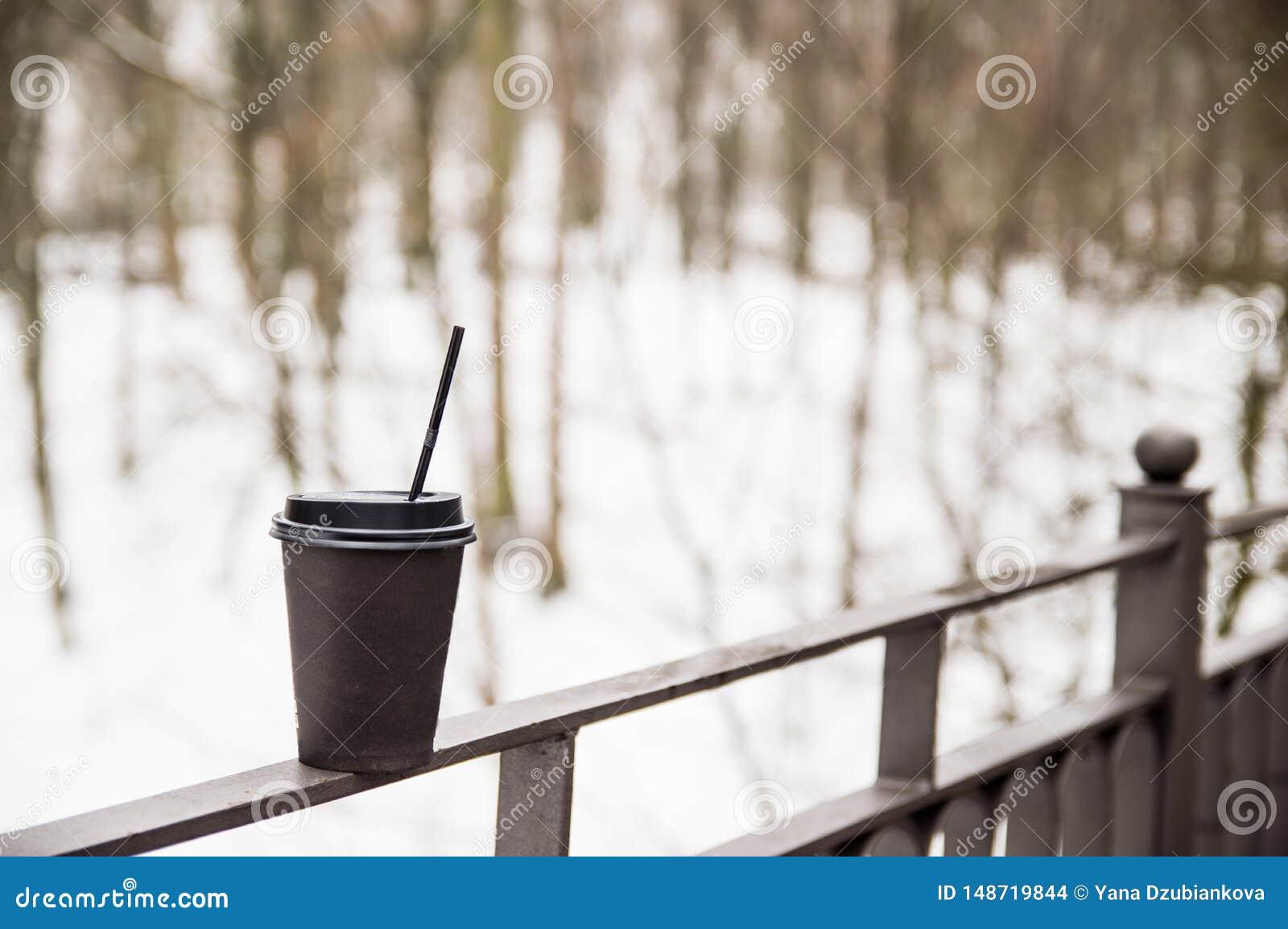 Tazza di carta con i supporti del caff? su un corrimano del metallo sul ponte