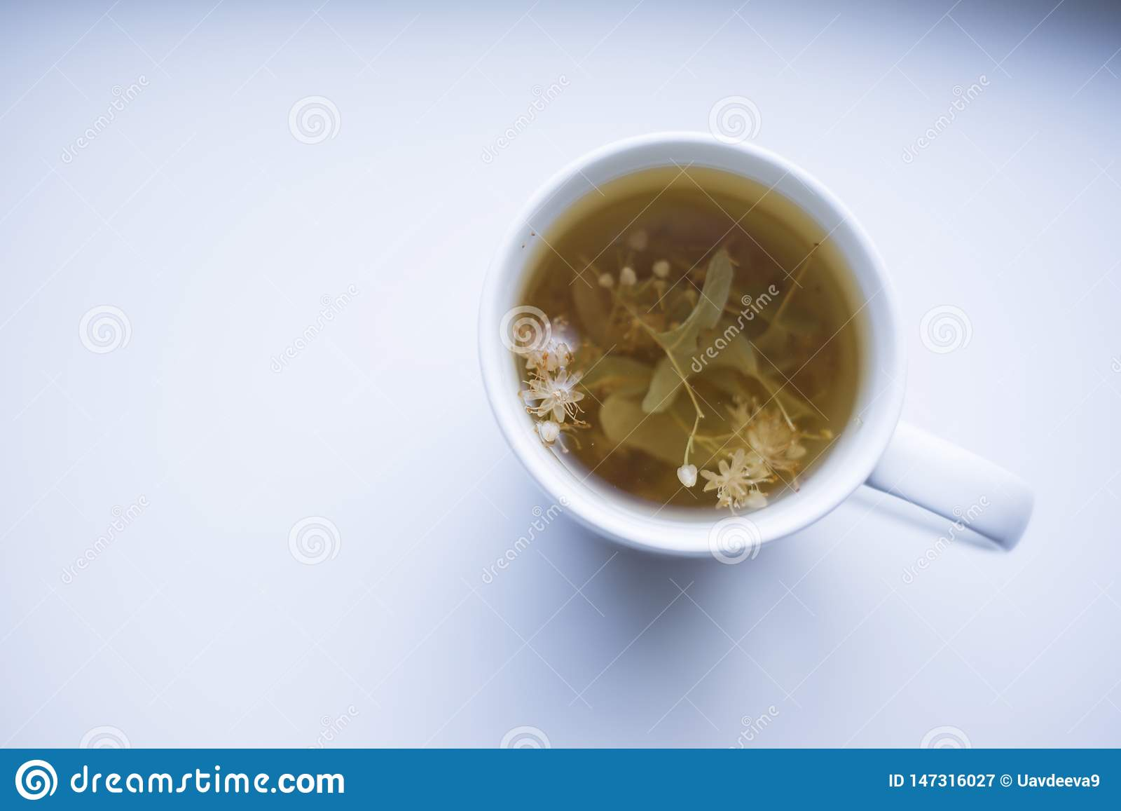 Tazza di erbe saporita di tè sulla tavola bianca