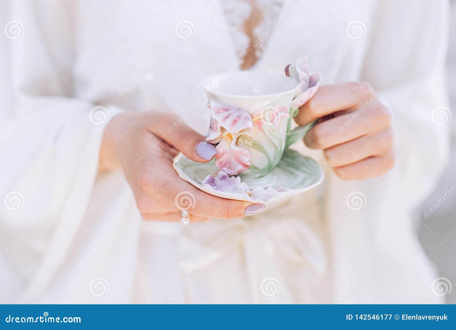 Tazza di mattina di tè in mani femminili