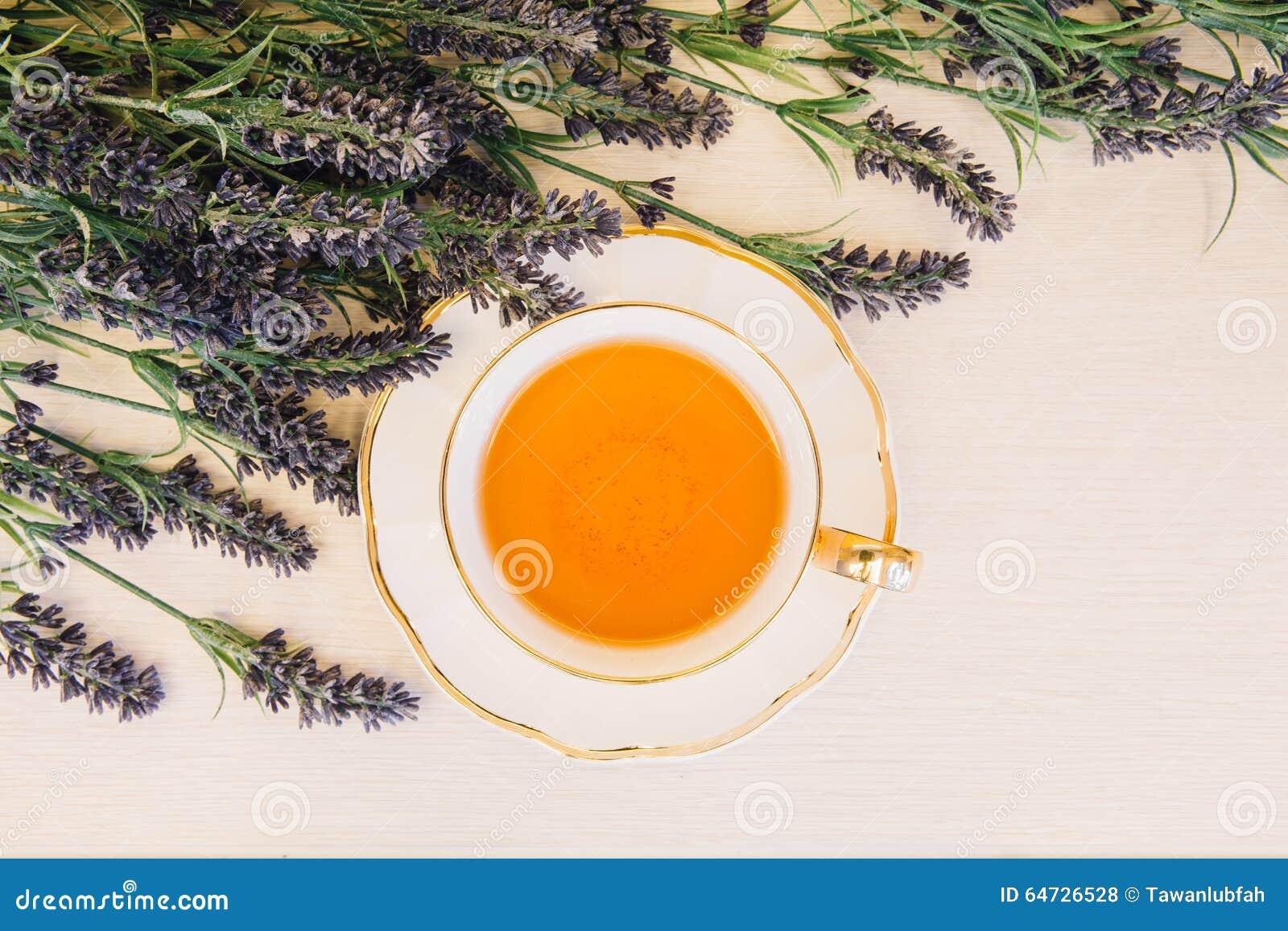 Tazza di tè con il fiore su una vista superiore del fondo di legno