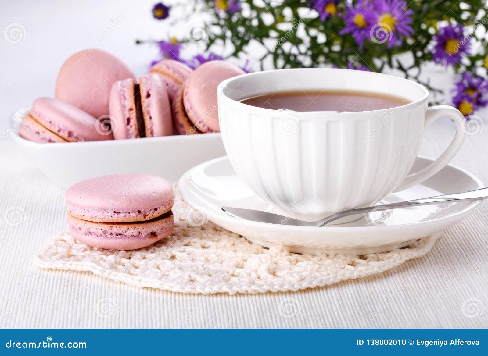 Tazza di tè e dei maccheroni rosa - biscotti francesi sulla tavola bianca