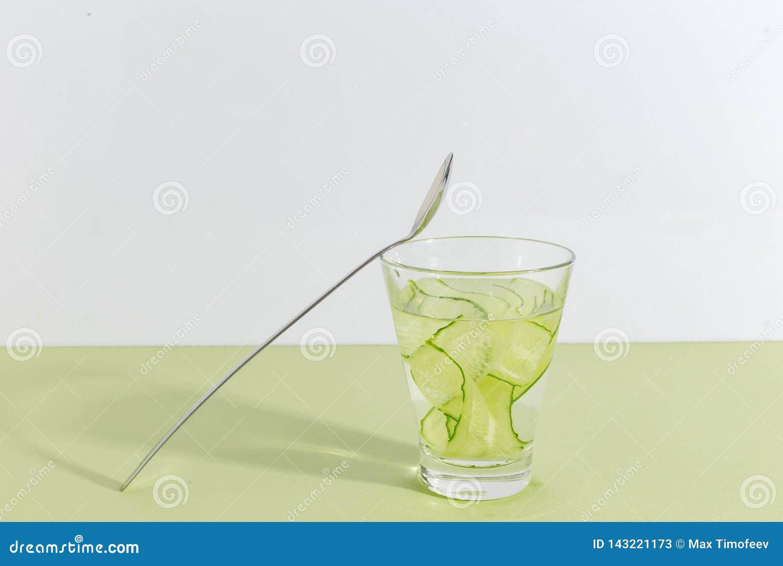 Tazza di vetro con acqua del cetriolo su un fondo verde chiaro Concetto creativo di Minimalistic Copi lo spazio