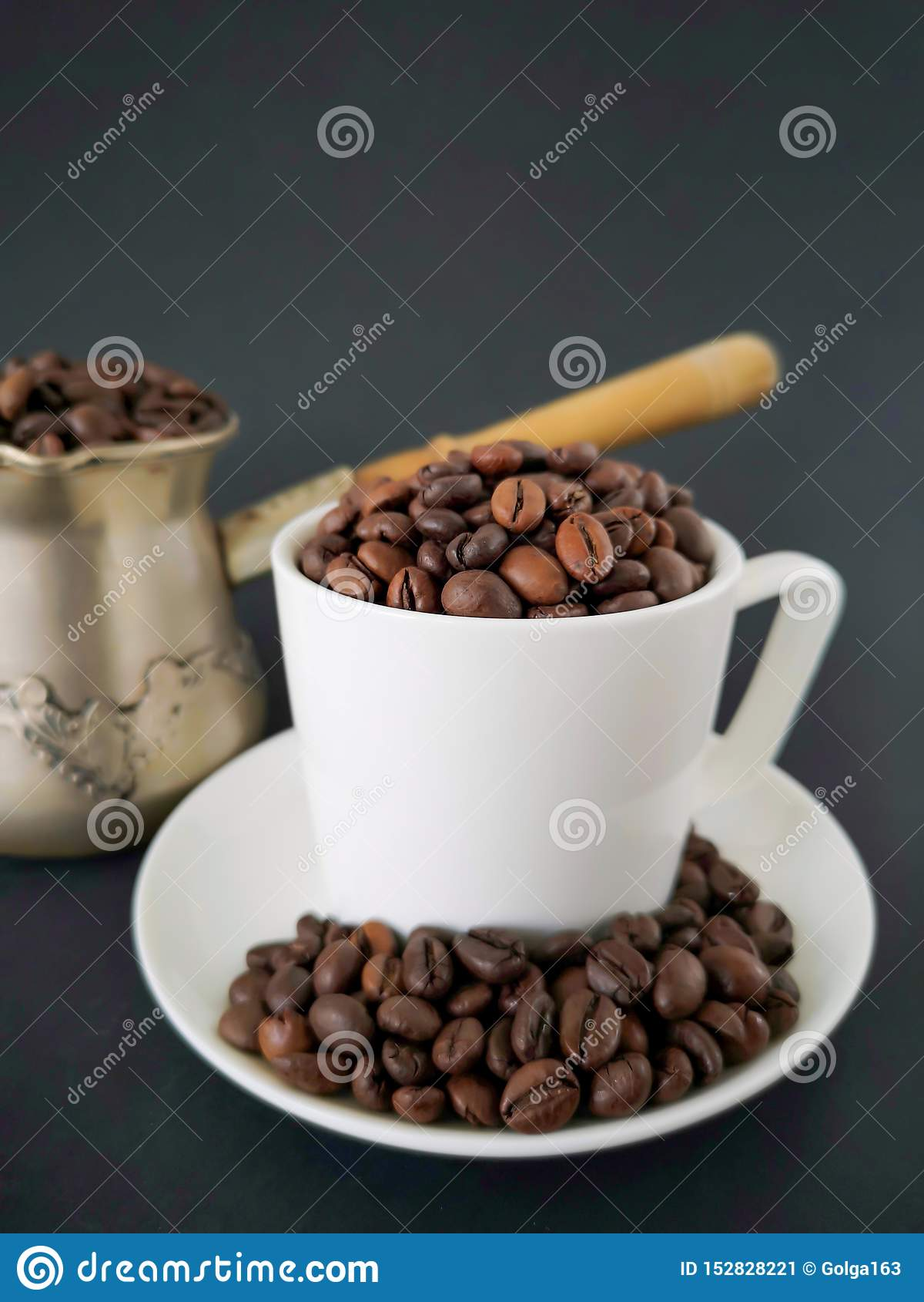 Tazza e piattino di caffè macchiato; chicchi di caffè sparsi sulla tavola Nei precedenti è un cezve Priorit? bassa nera