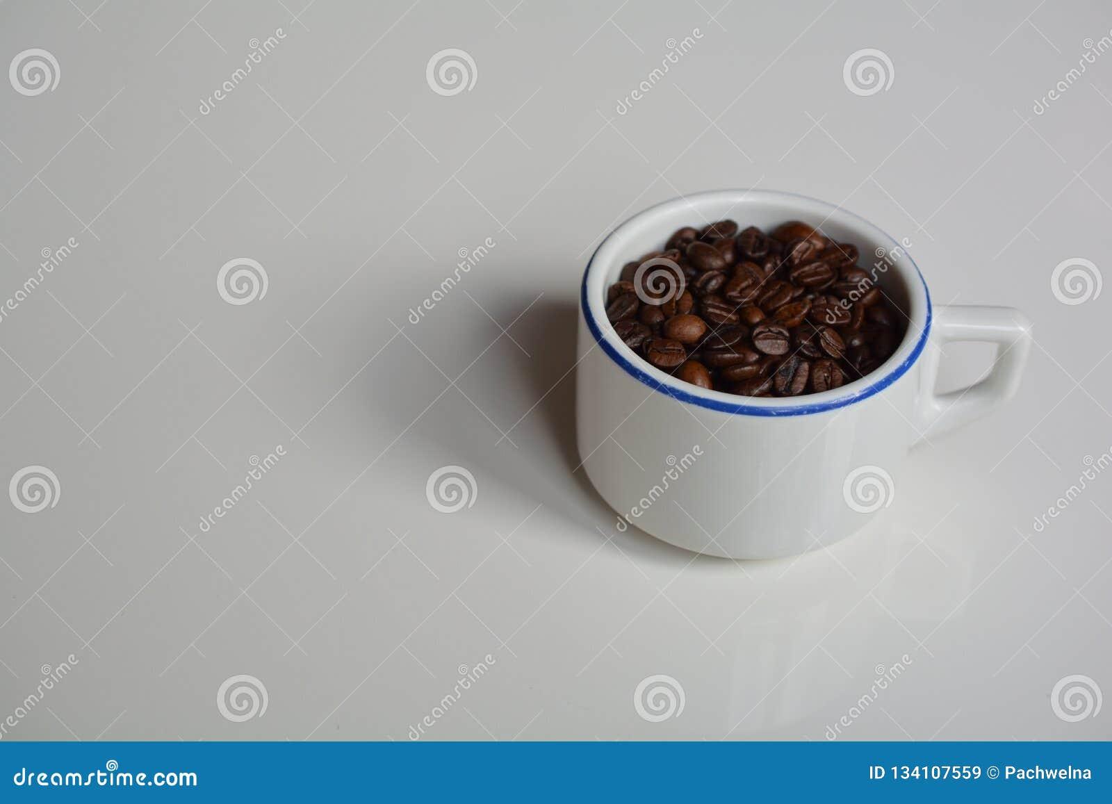 Tazza a pareti spesse riempita di chicchi di caffè