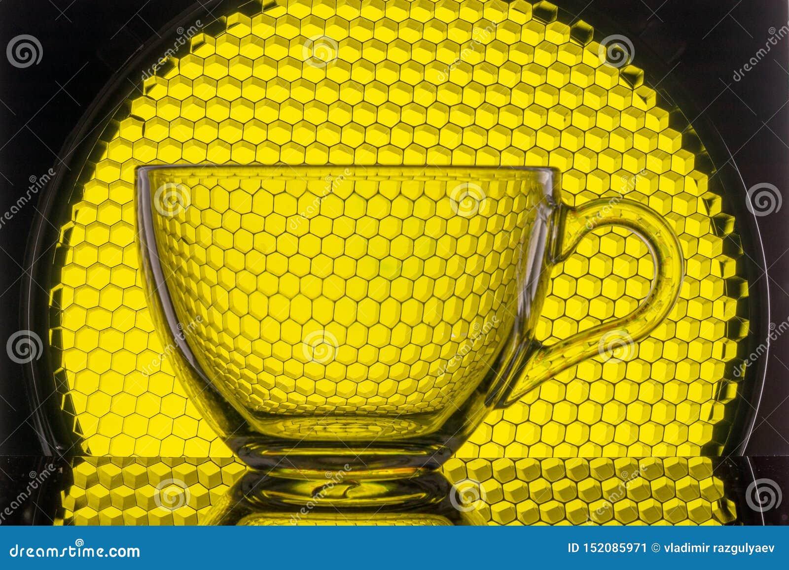 Tazza trasparente su un fondo del favo giallo per fotografia