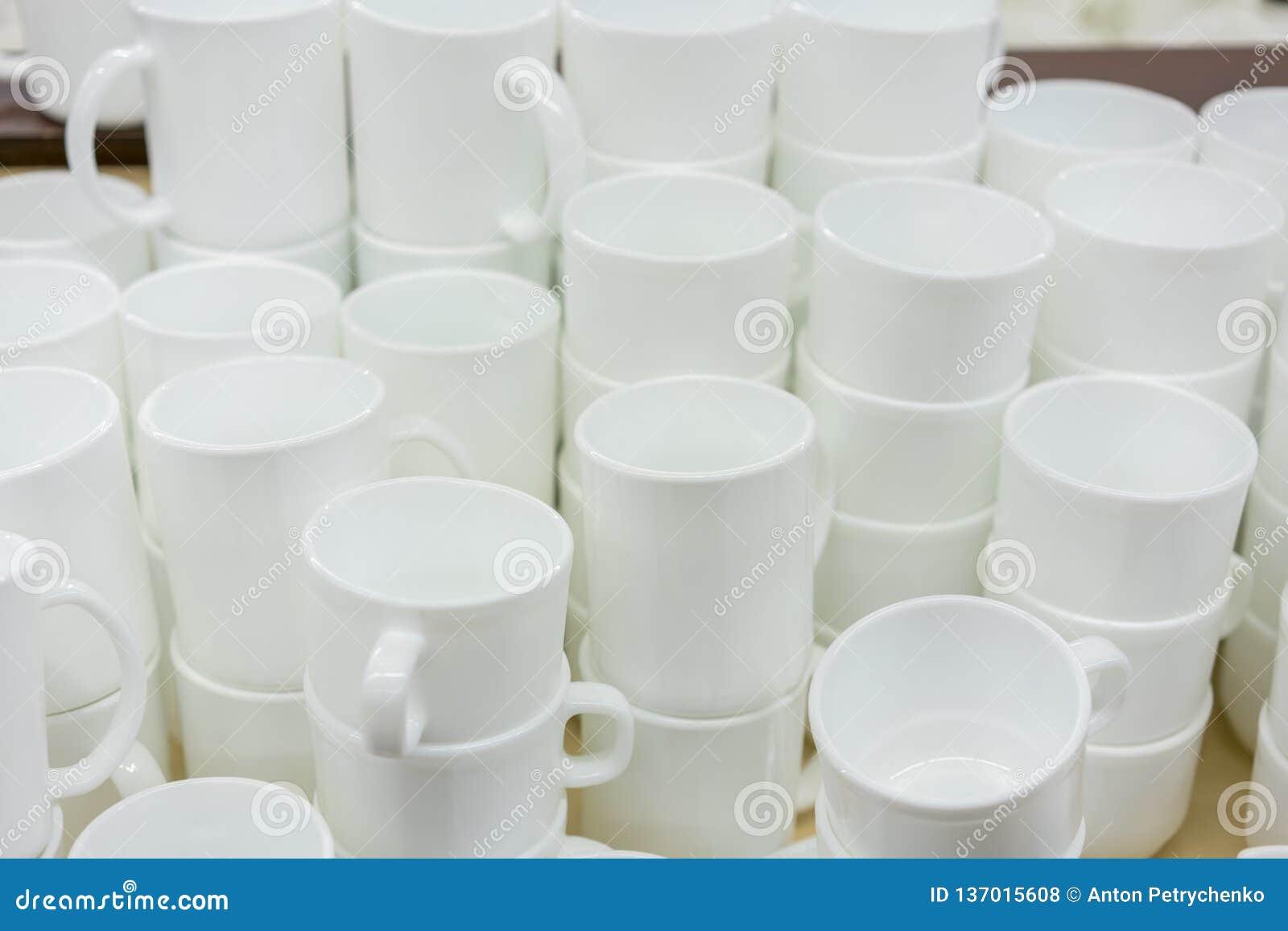Tazze bianche sullo scaffale nel deposito Tazze e piattini di caffè ceramici bianchi sugli scaffali Scaffali con gli utensili del