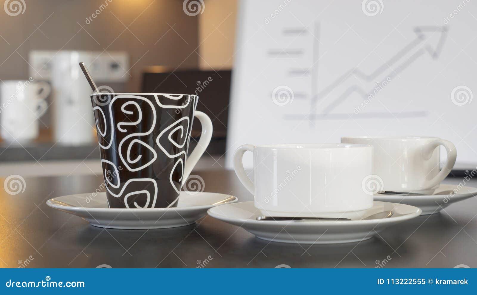 Credenza Con Tazze : Tazze di tè e del caffè su una credenza davanti ad un grafico
