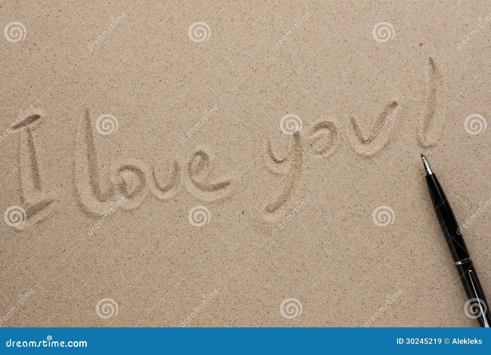 Amor Escrito En Arena: Te Amo Escrito En Pluma En La Arena Imágenes De Archivo