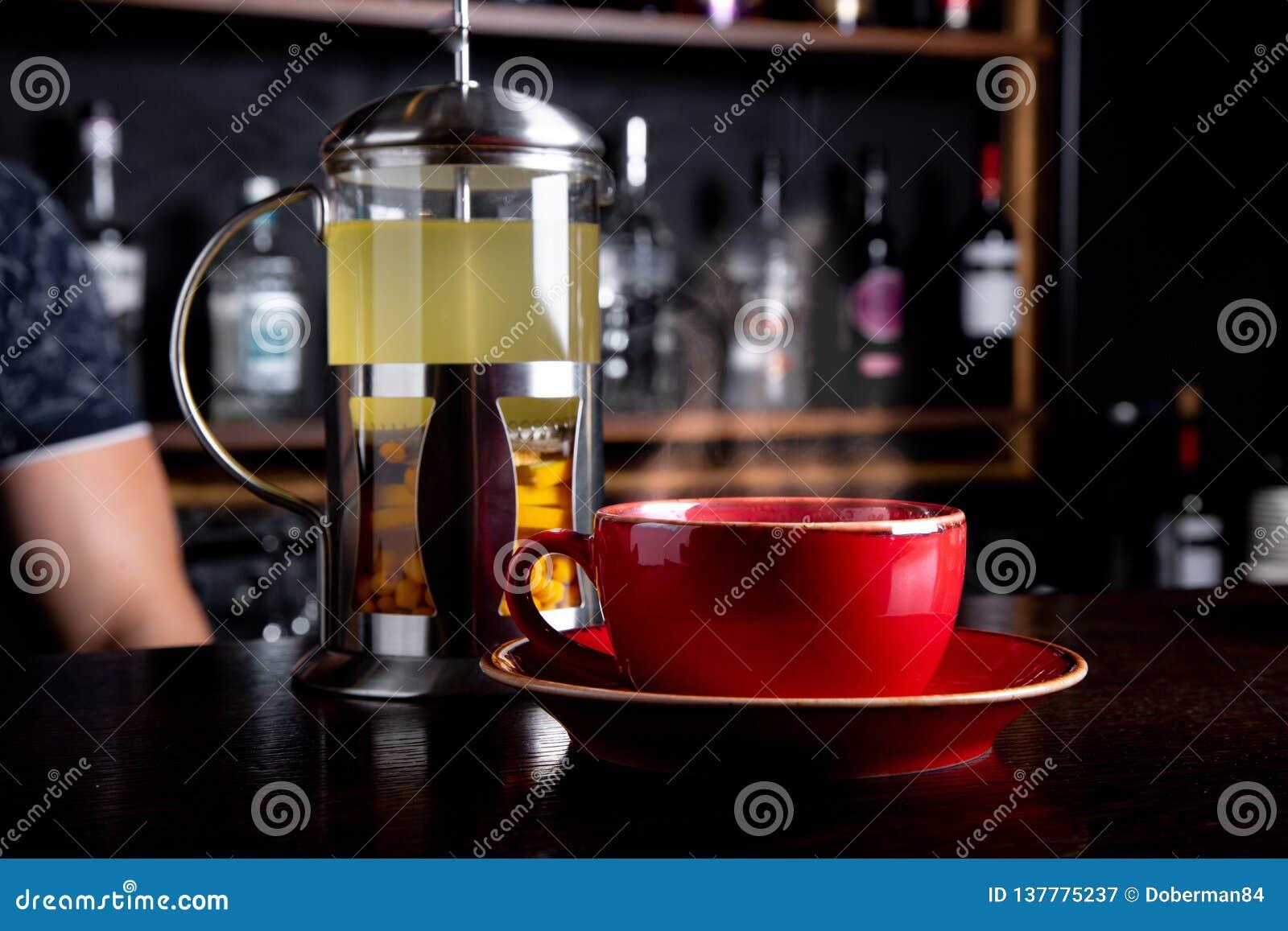 Te för havsbuckthorn i fransk press på en stångbakgrund på coffee shop