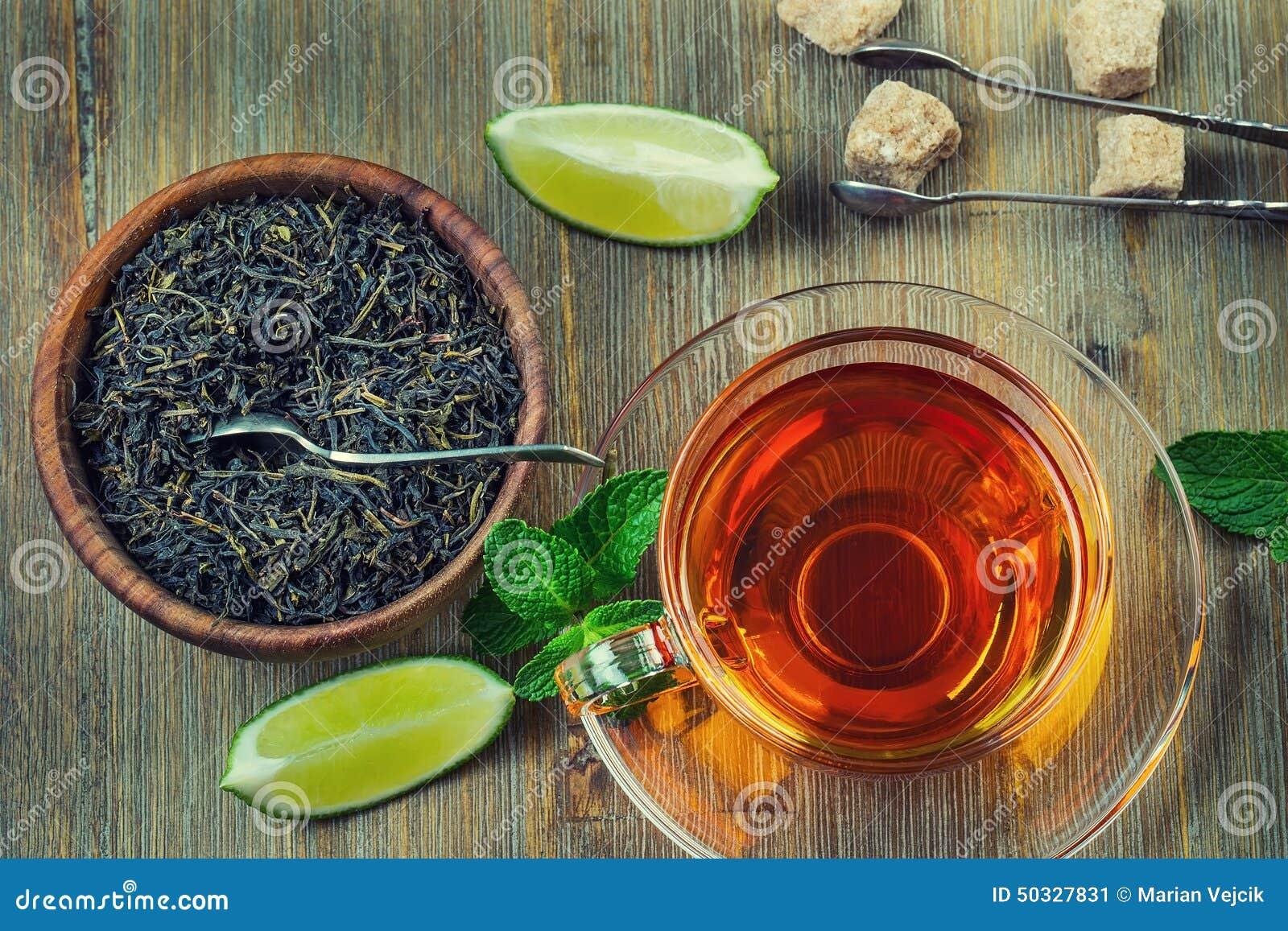 Te i en glass kopp, mintkaramellsidor, torkade te, skivad limefrukt, rottingsocker