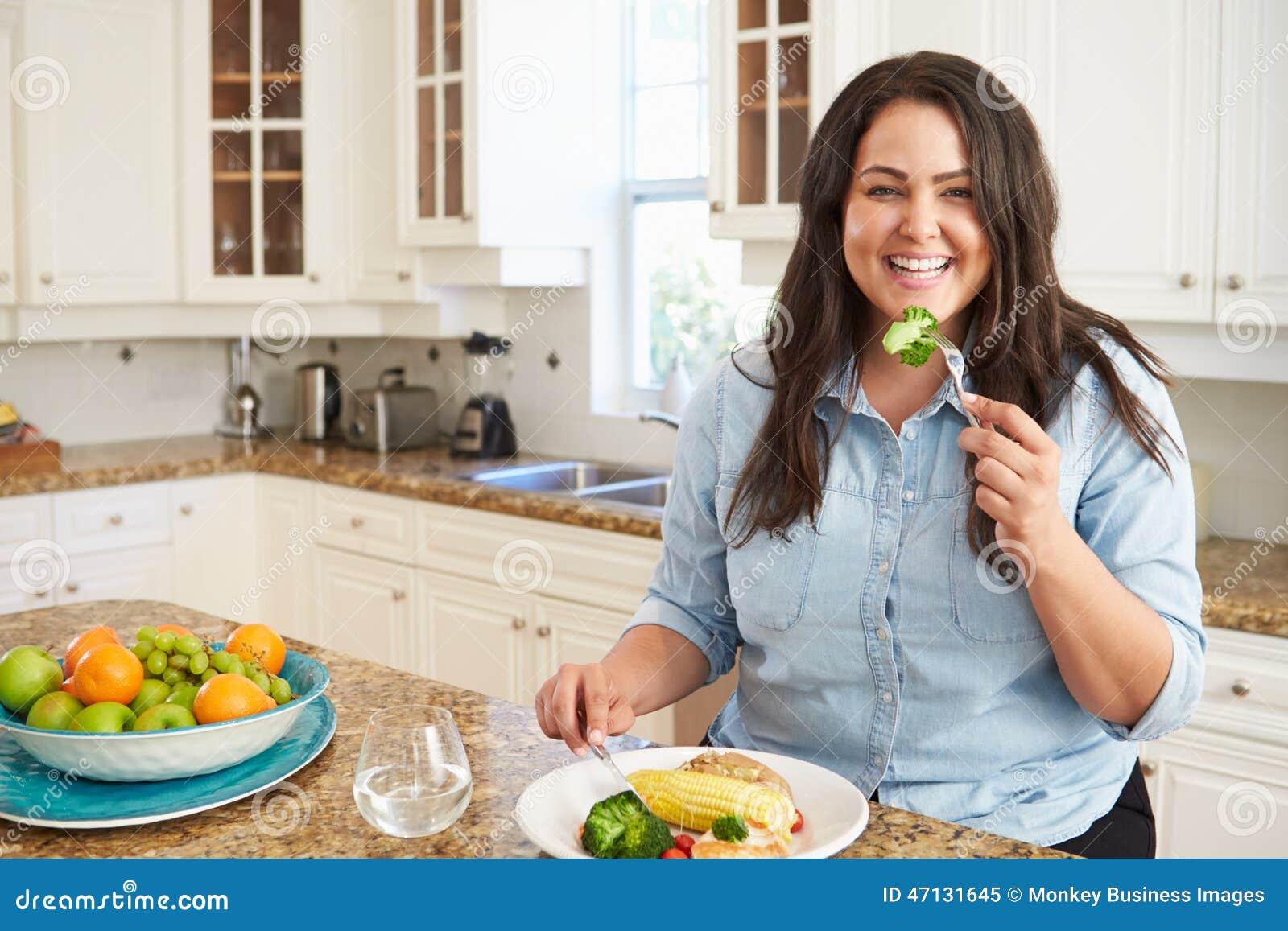 Te zware Vrouw die Gezonde Maaltijd in Keuken eten