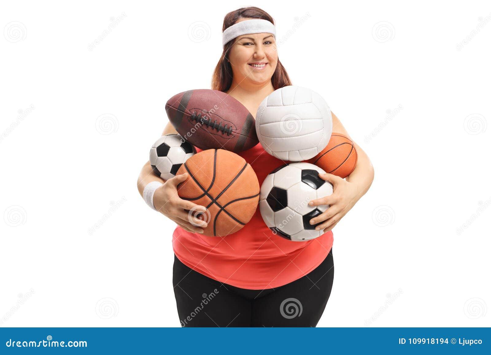 Te zware vrouw die verschillende soorten sportenballen houden
