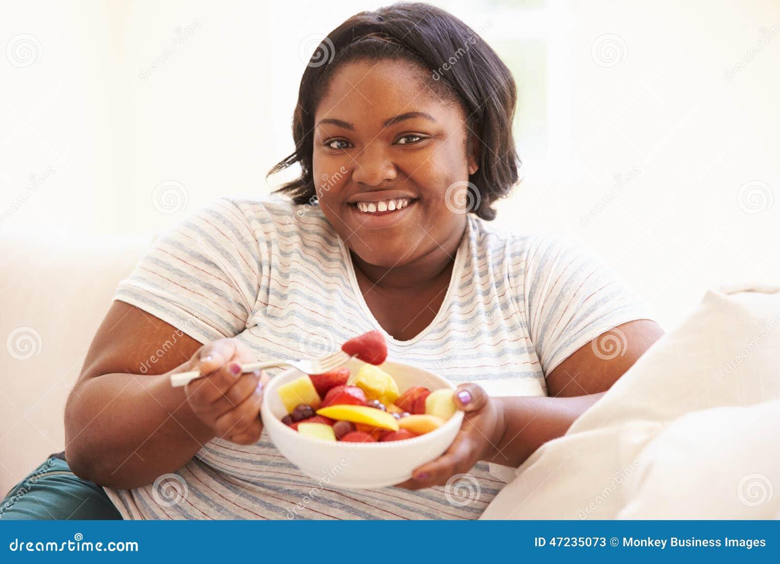 Te zware Vrouwenzitting op Sofa Eating Bowl Of Fresh-Fruit
