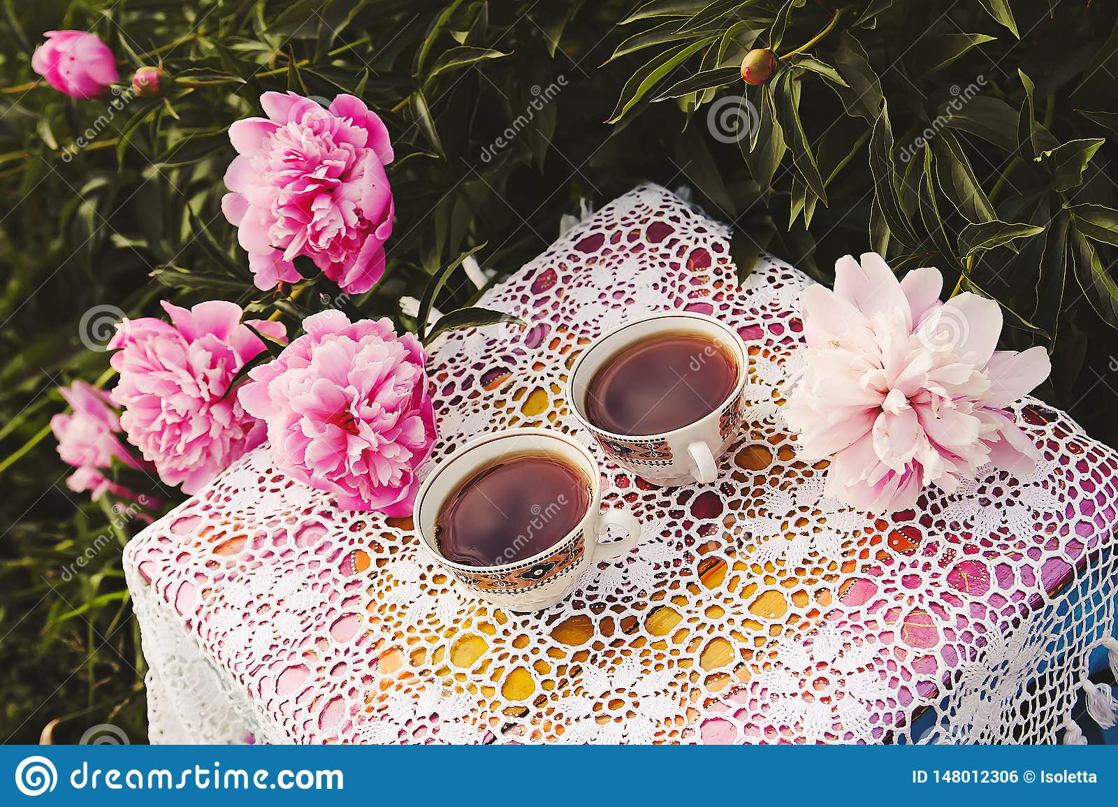 Tea in country style in summer garden. Two cups of black tea on handmade crocheted vintage lacy tablecloth and blooming peony