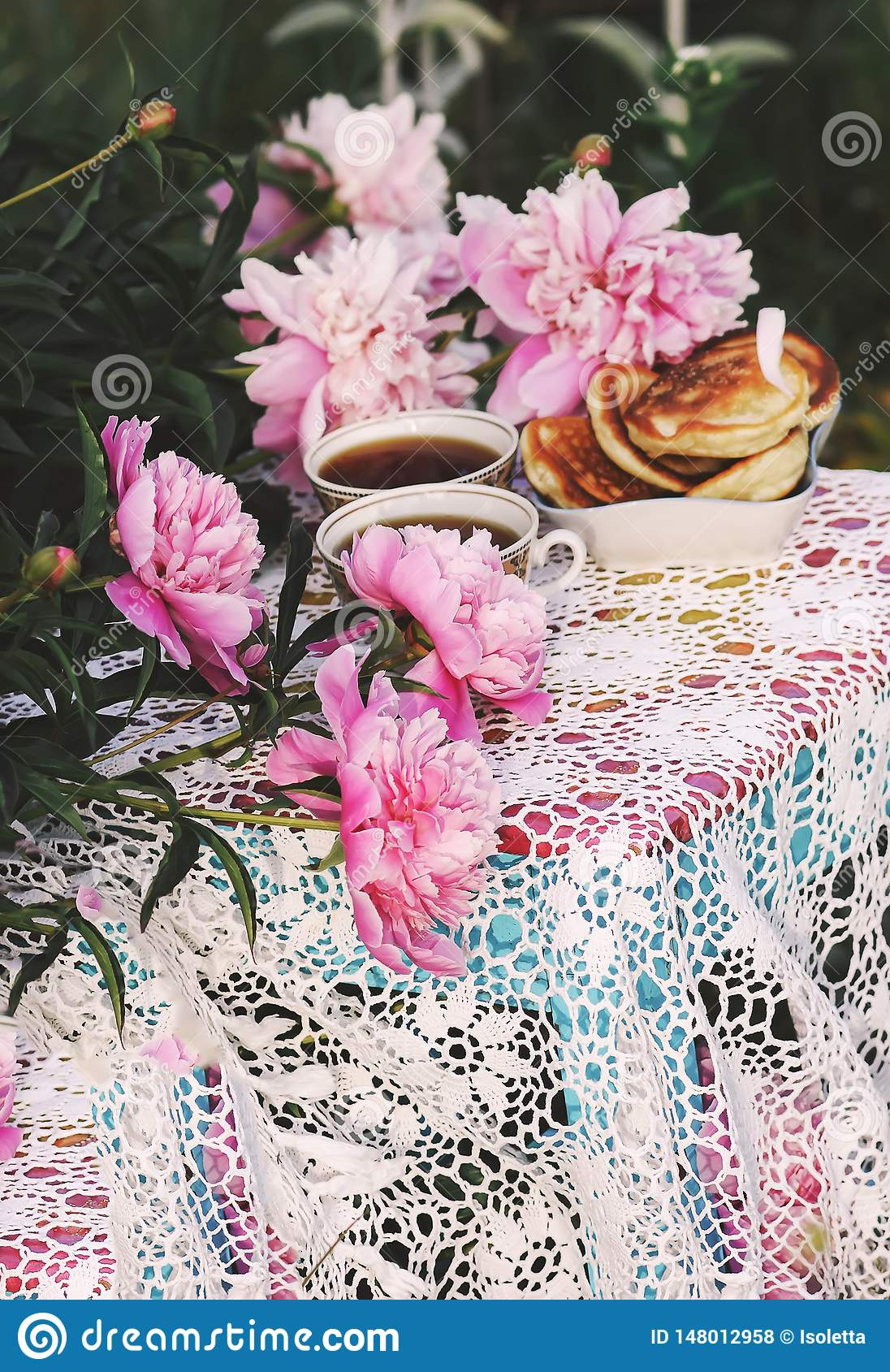 Tea in country style in summer garden. Two cups of black tea and pancakes on handmade crocheted vintage lacy tablecloth and